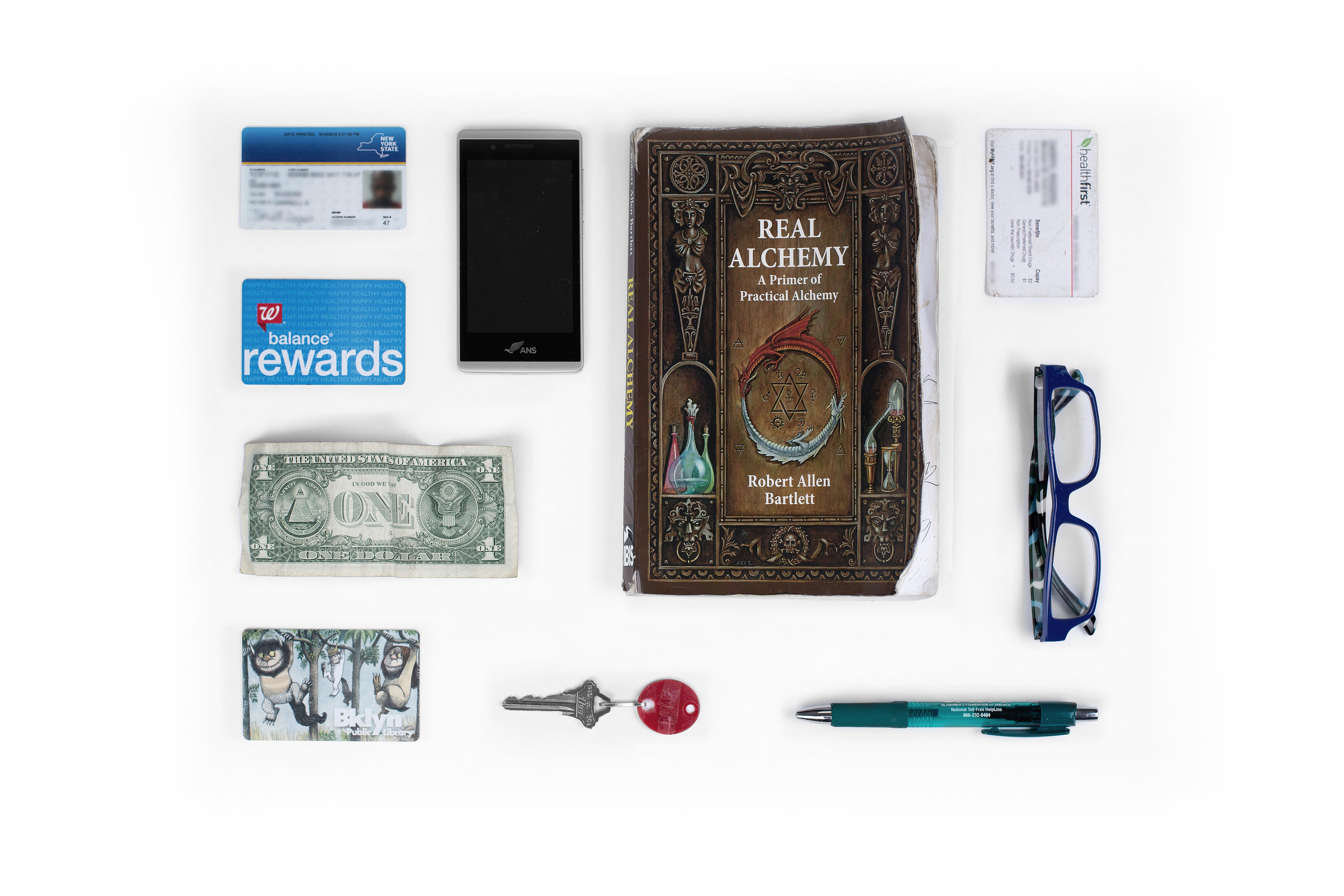 "New York State ID – Cell Phone – ""Real Alchemy"" Book – Health Insurance Card – Walgreens Rewards Card – $1 Bill – Reading Glasses – Library Card – Key to Storage Locker – Pen"
