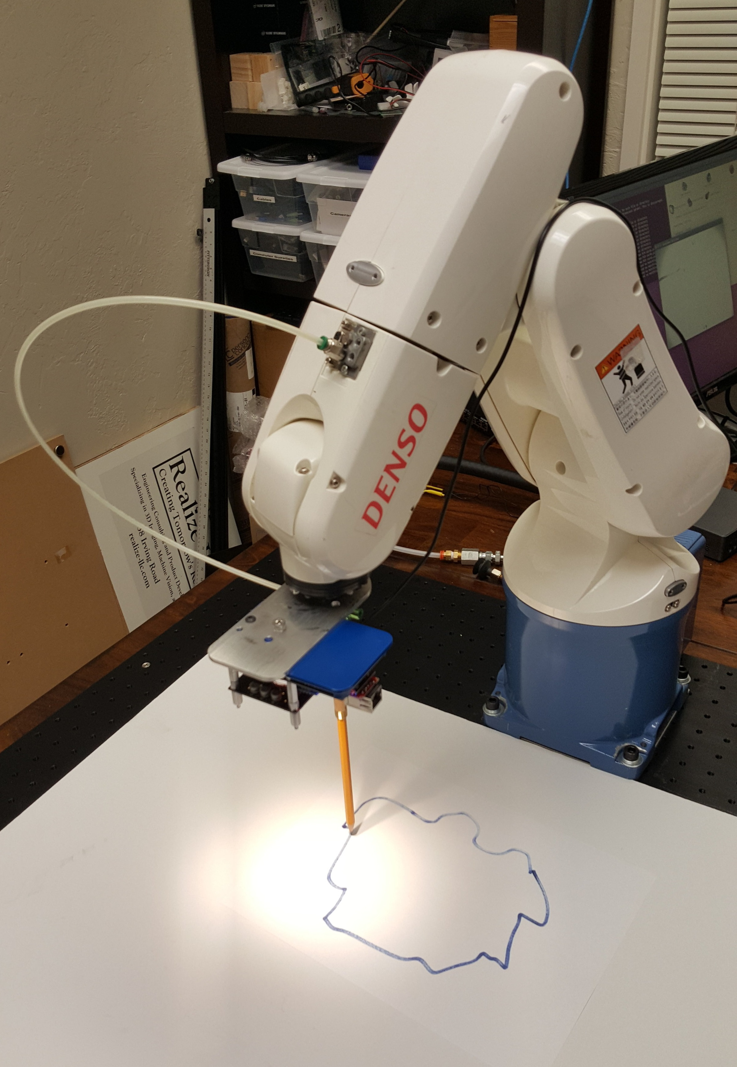 Following a Line   There are many applications that require following a templated line or pattern in order to cut a shape out of a piece of material. Rigid materials such as steel are fairly straightforward for traditional robots to follow a pattern.  But what happens if the material is flexible like  rubber ,  fabric , or  plastic ? What if it moves or deforms while being cut? That would require a vision system that can maintain its course even when things move a bit, like our  Vision-in-Motion  technology can do. We're currently working on a research project for a large manufacturer facing exactly that problem. In this image we're investigating the tracing of an outline using a pencil as a stylus.