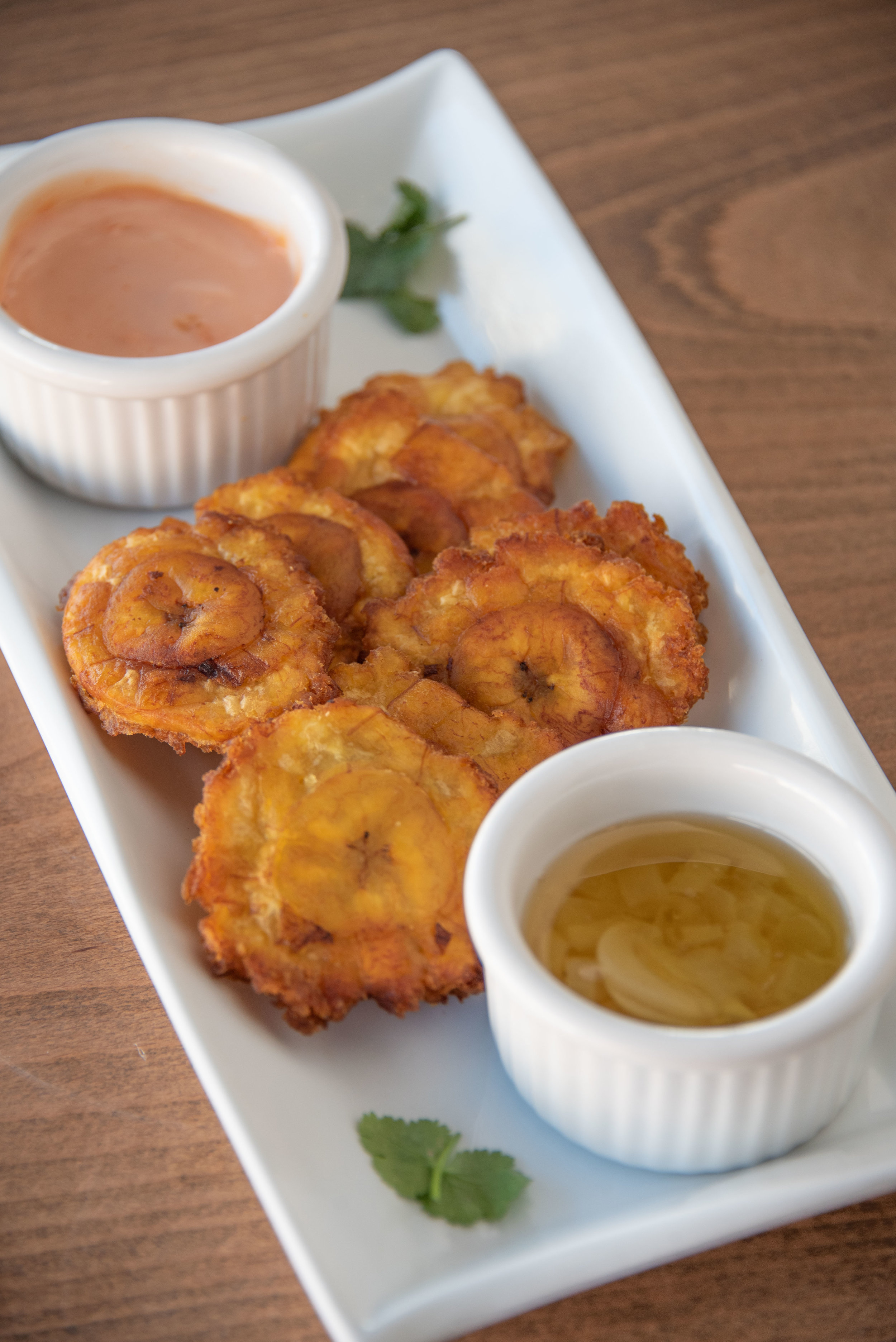 Crispy Tostones twice-fried Green Plantains served with two sauces, Garlic Mojo and Spicy Remoulade