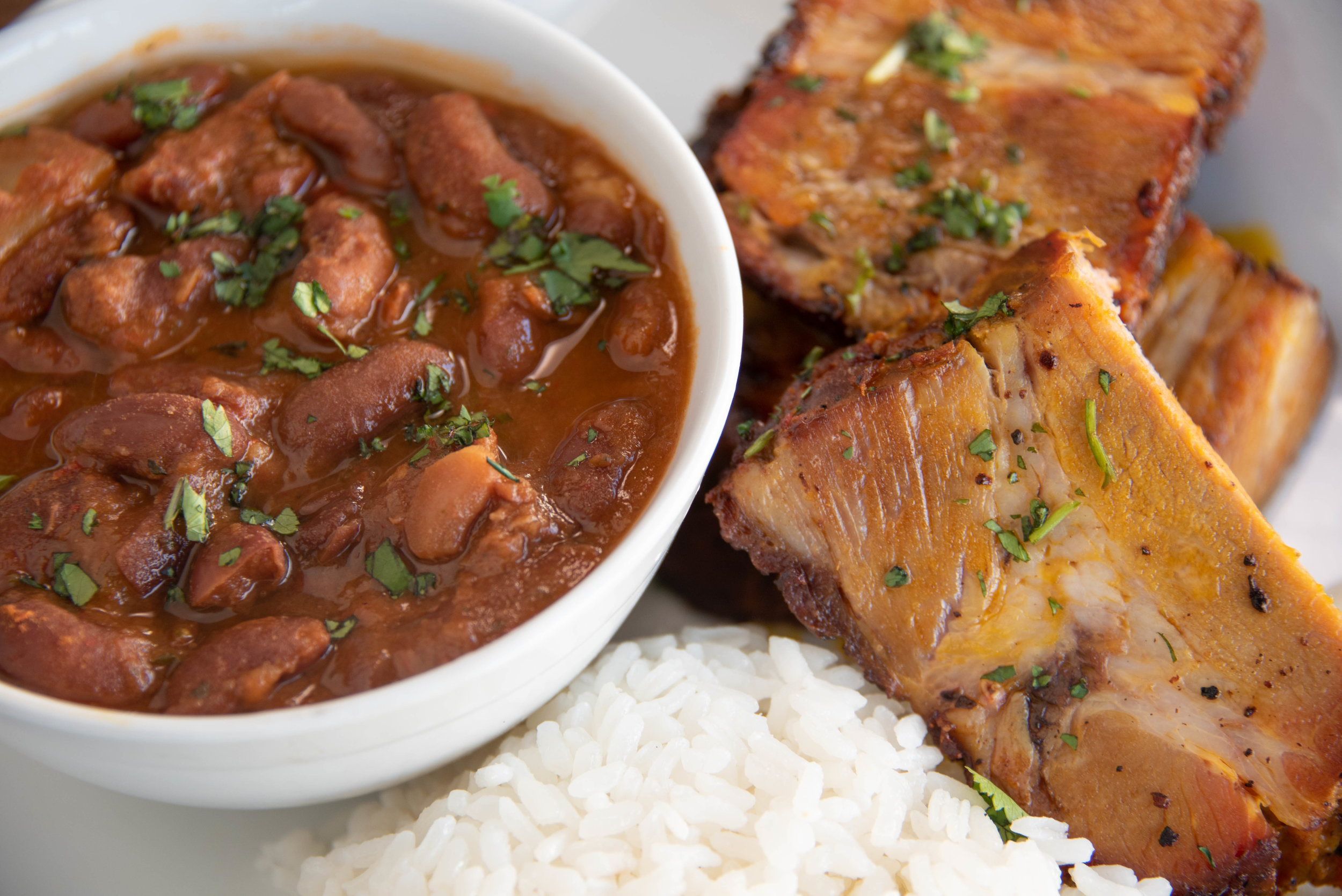 Flavorful slices of Pernil — Slow Roasted Pork Shoulder marinated with Spices, Garlic and Fresh Oregano— with Arroz Blanco and a warm bowl of Habichuelas