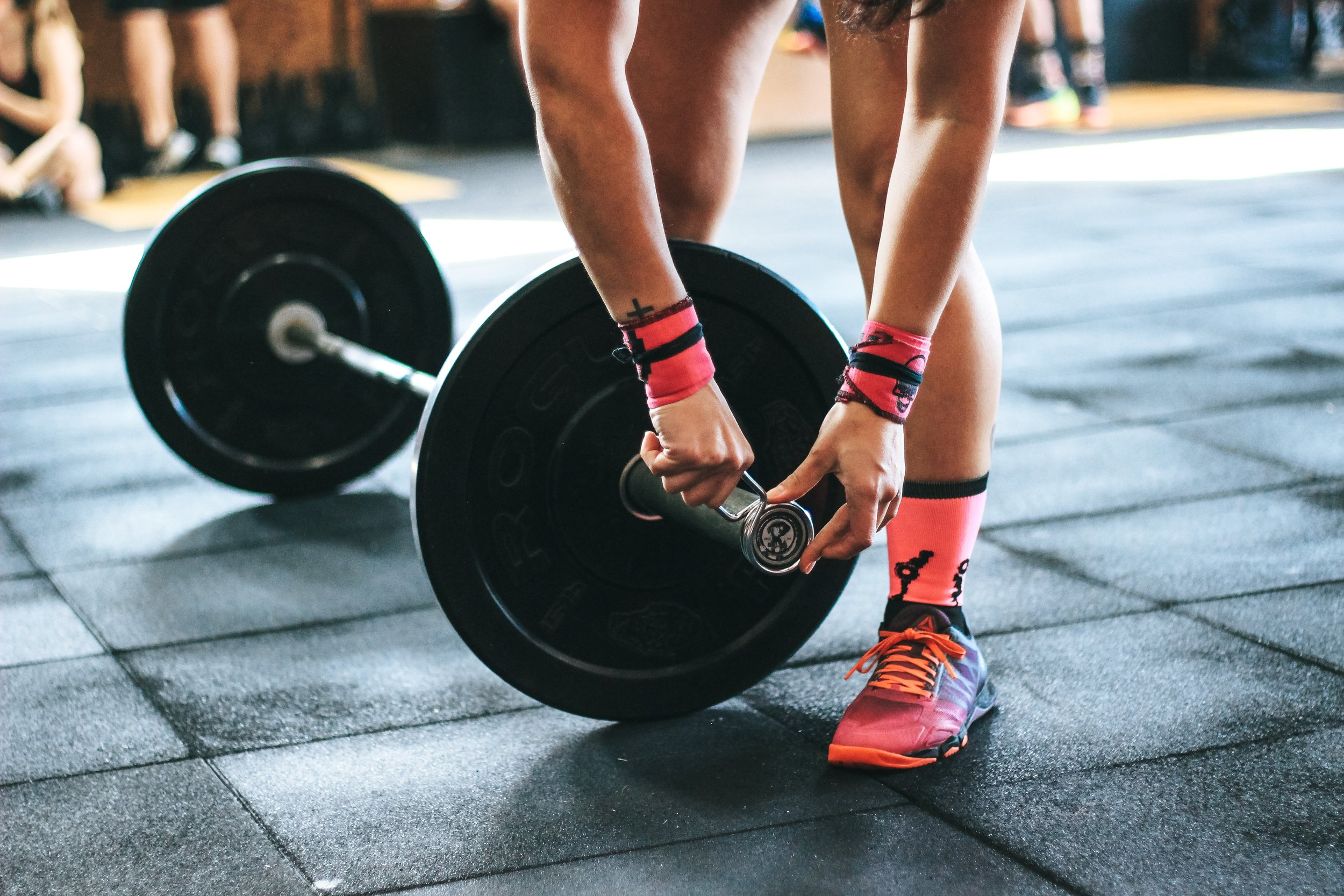 Girl with supplements, pink trainers and wrist wraps gear doing barbell workout