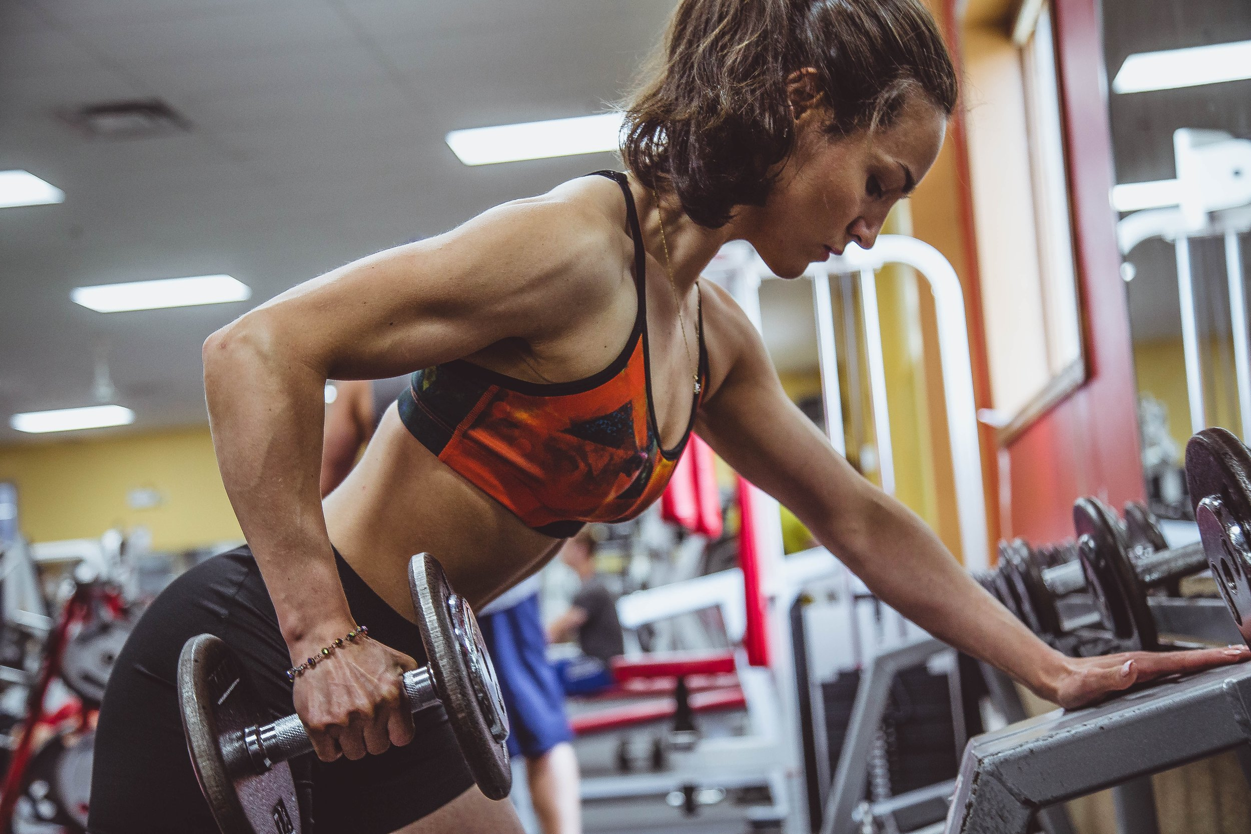 female with supplements doing dumbell workout