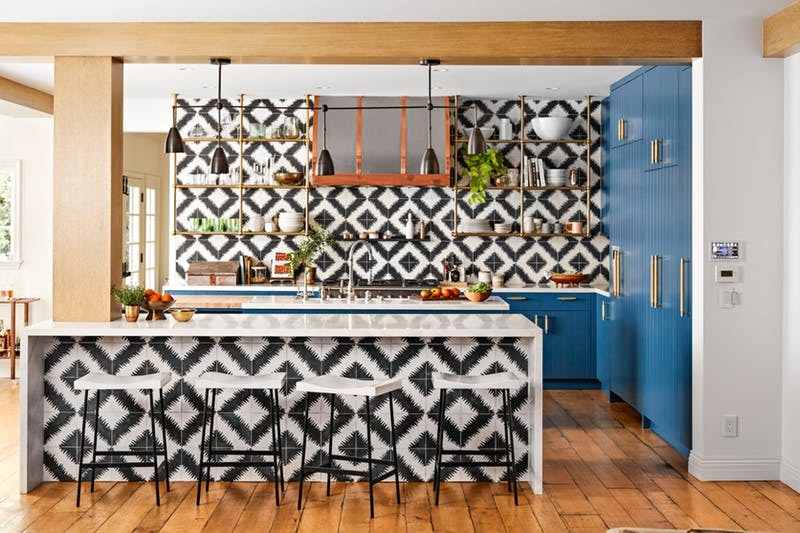 Blue cabinets and graphic black and white tiles make the kitchen of Hilary Duff extra popping | photos by  Justin Coit