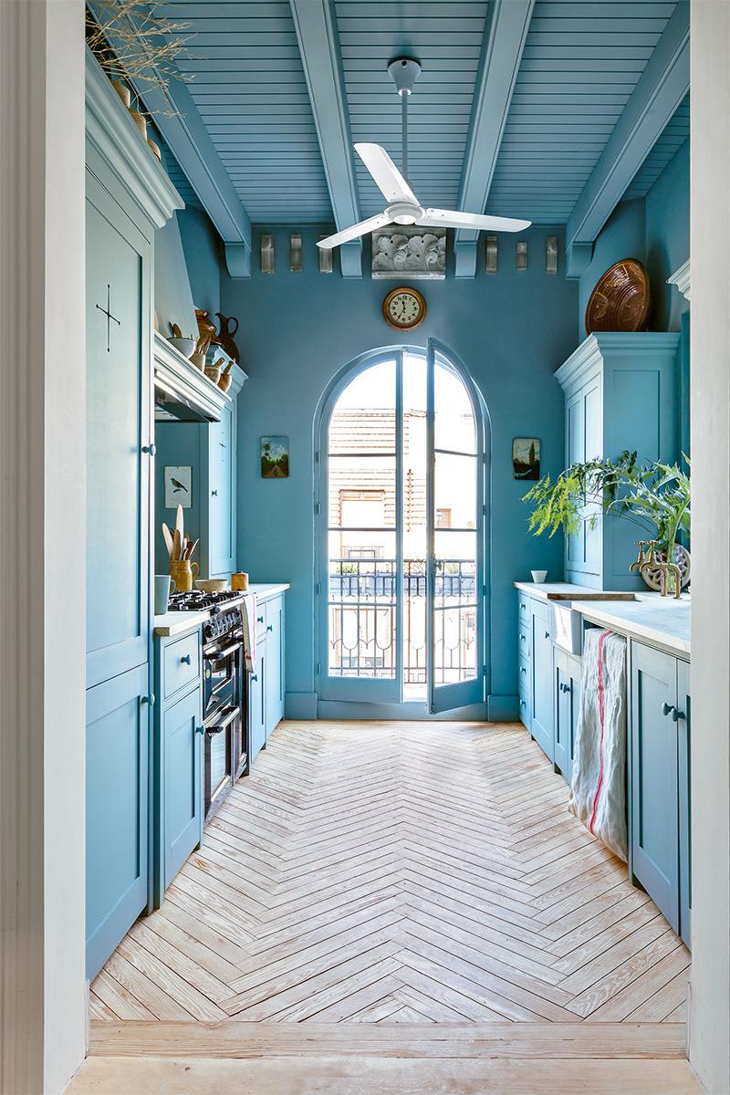 Не только синие шкафы, но и синие стены и потолок, безусловно, выделяют эту кухню. Красивый деревянный пол придает этой кухне немного тепла и умиротворения   фото Рикардо Лабугла