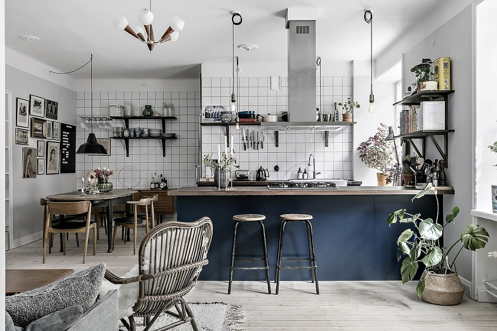 A blue kitchen with a cool tiled dining space
