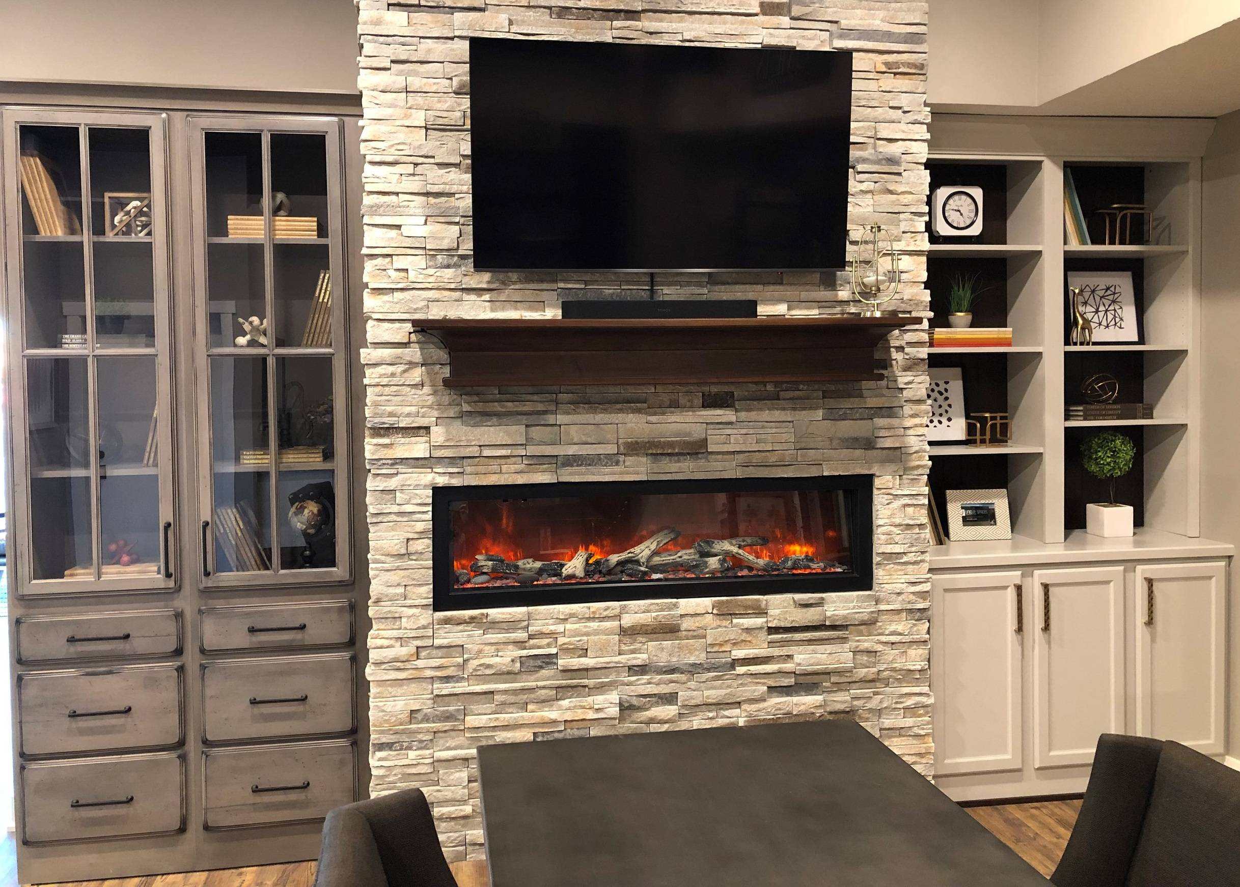 Fireplace - StarMark Cabinetry - Tudor door style in Alder finished with Driftwood stain with Ebony glaze and Deco Edge finish (left)StarMark Cabinetry - Seneca door style in Maple finished with Repose Grey tinted varnish (right)