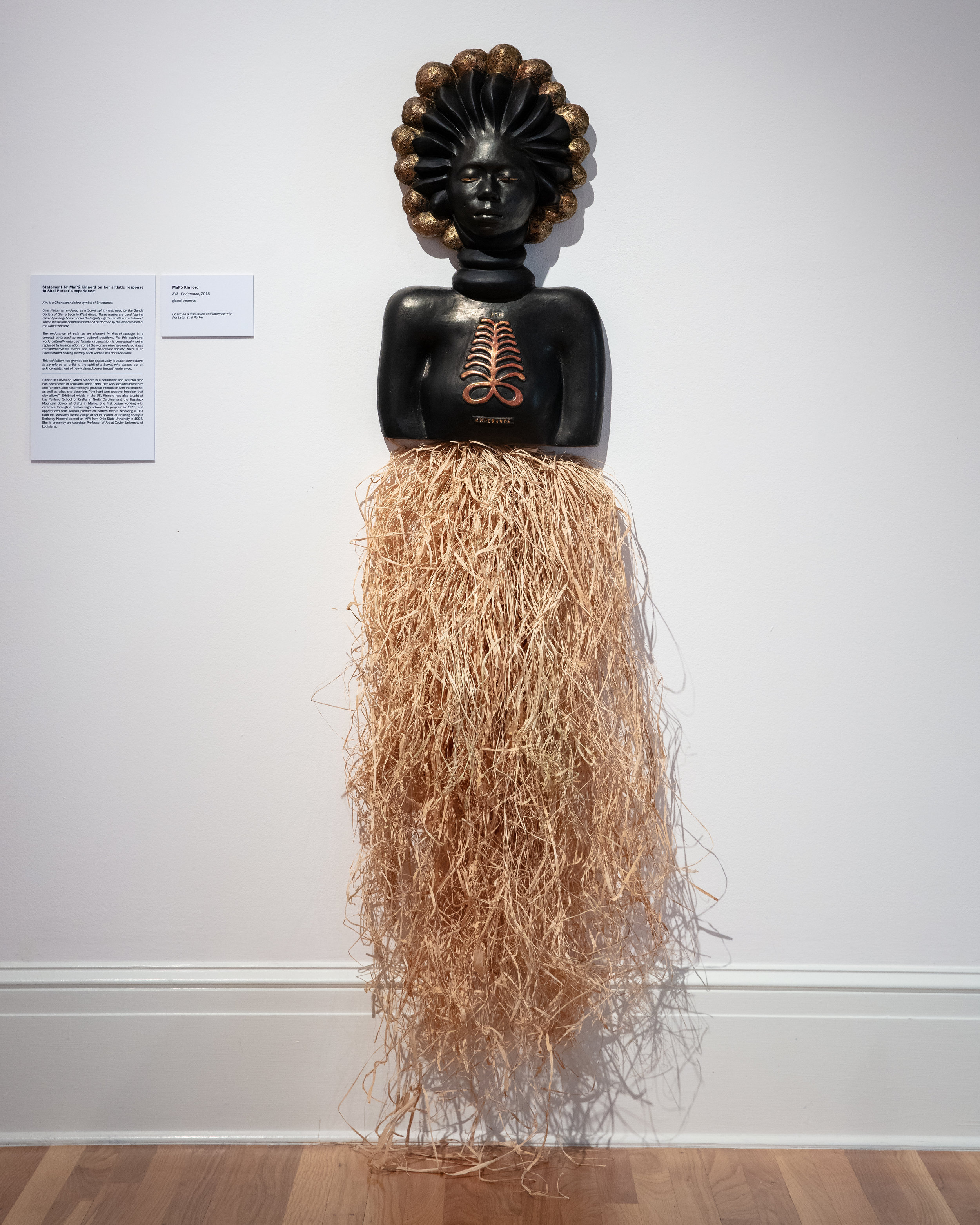 """Artist Statement - AYA – is a Ghanaian Adinkra symbol meaning Endurance.Shai Parker is rendered as a Sowei spirit mask used by the Sande Society of Sierra Leon in West Africa. These masks are used """" during rites-of-passage"""" ceremonies that signify a girl's transition to adulthood."""" These masks are commissioned and performed by the elder women of the Sande society.The endurance of pain as an element in rites-of-passage is a concept embraced by many cultural traditions. For this sculptural work, culturally enforced female circumcision is conceptually being replaced by incarceration. For all the women who have endured these transformative life events and have """"re-entered society"""" there is an uncelebrated healing journey each woman will not face alone. For me this exhibition has granted me the opportunity to make connects to my role as an artist to the spirit of a Sowei who dances out an acknowledgement of newly gained power through endurance.- MaPó KinnordAYA-Endurance, 2018"""