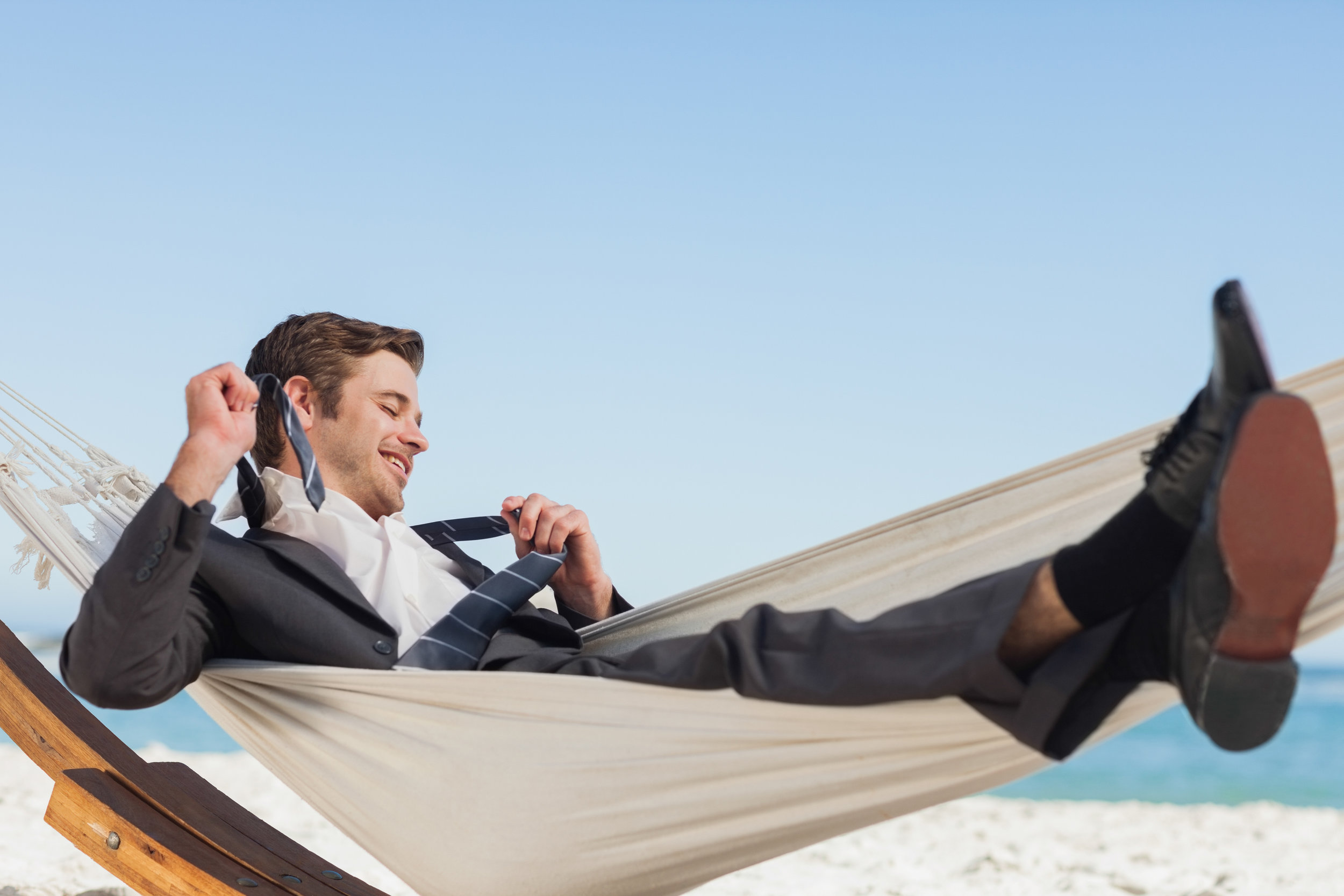 Smiling-businessman-lying-in-hamock-taking-off-his-tie-503070669_3869x2579.jpeg