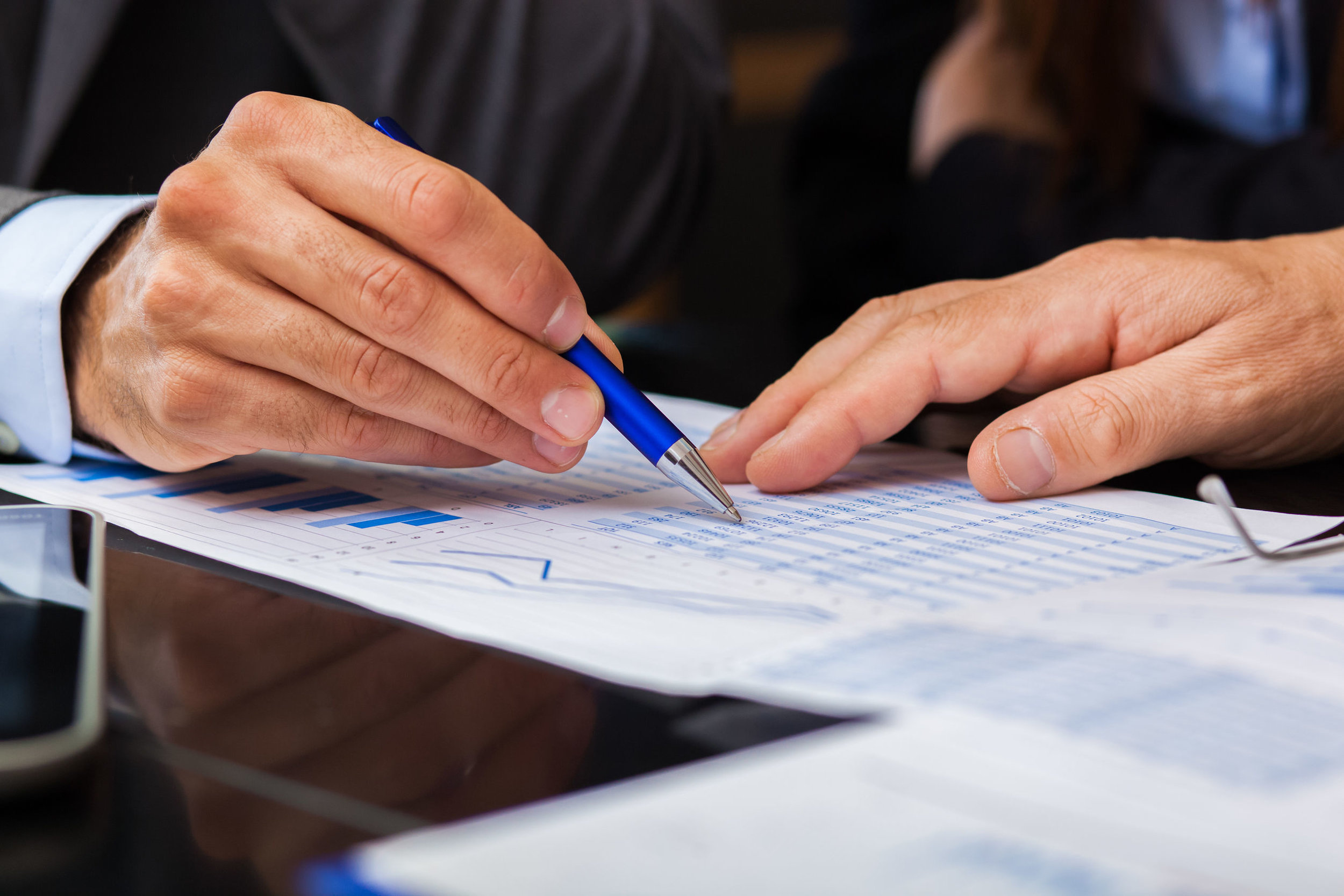 Close up photo of team member writing on financial document. Links to Our Services page.