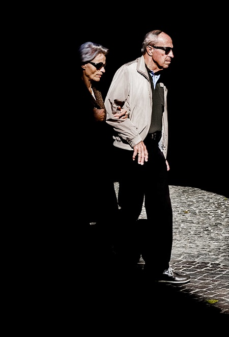 An elderly man leads an elderly woman out of darkness.