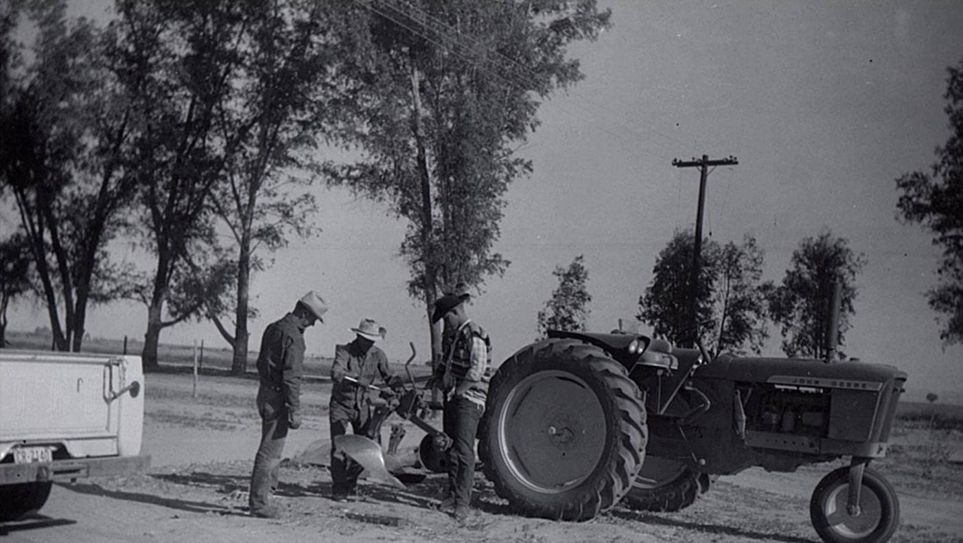 Selwyn the elder hooking a plow up to a JD 3010 with a young DeWayne supervising.
