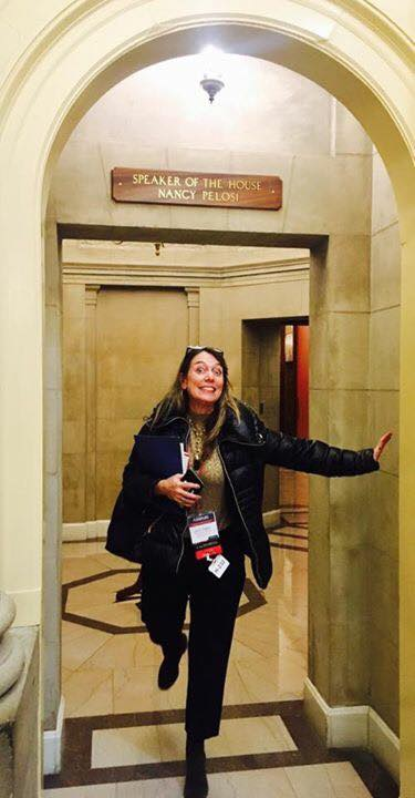 Executive Director Julie Baker strikes a pose in front of Speaker Pelosi's office.