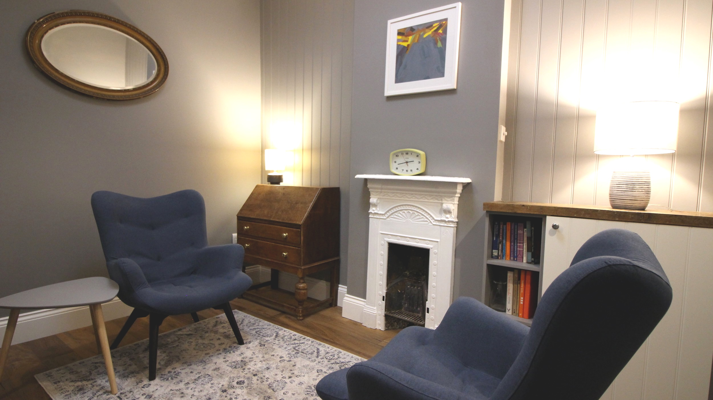 study - A beautiful room with ambient lighting contains two comfortable armchairs, a desk and additional chair.