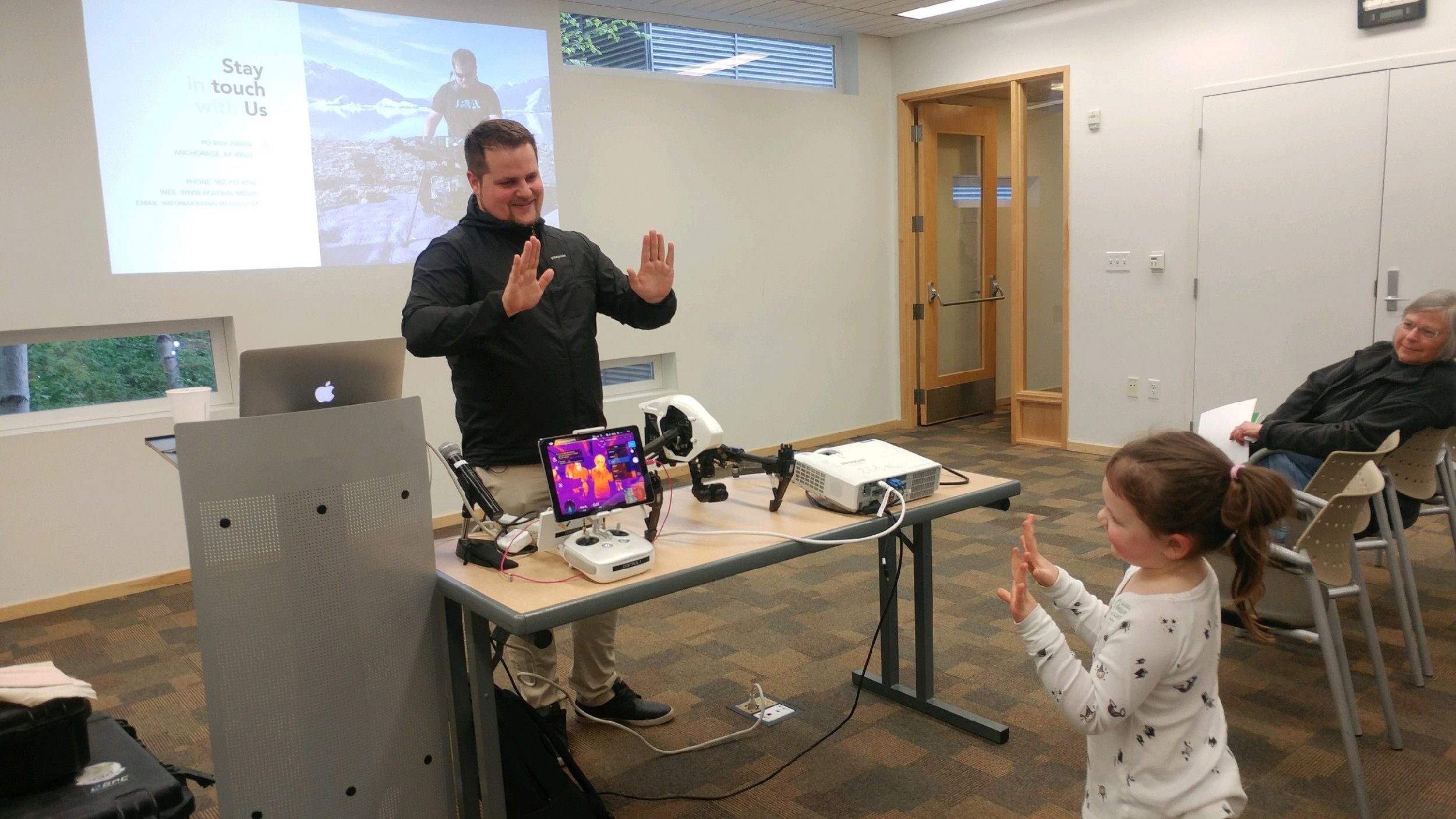 Presenter Ryan Marlow, Co-Founder of Alaska Aerial Media, shows Ellie how drones can use heat sensing technology to detect whales under water