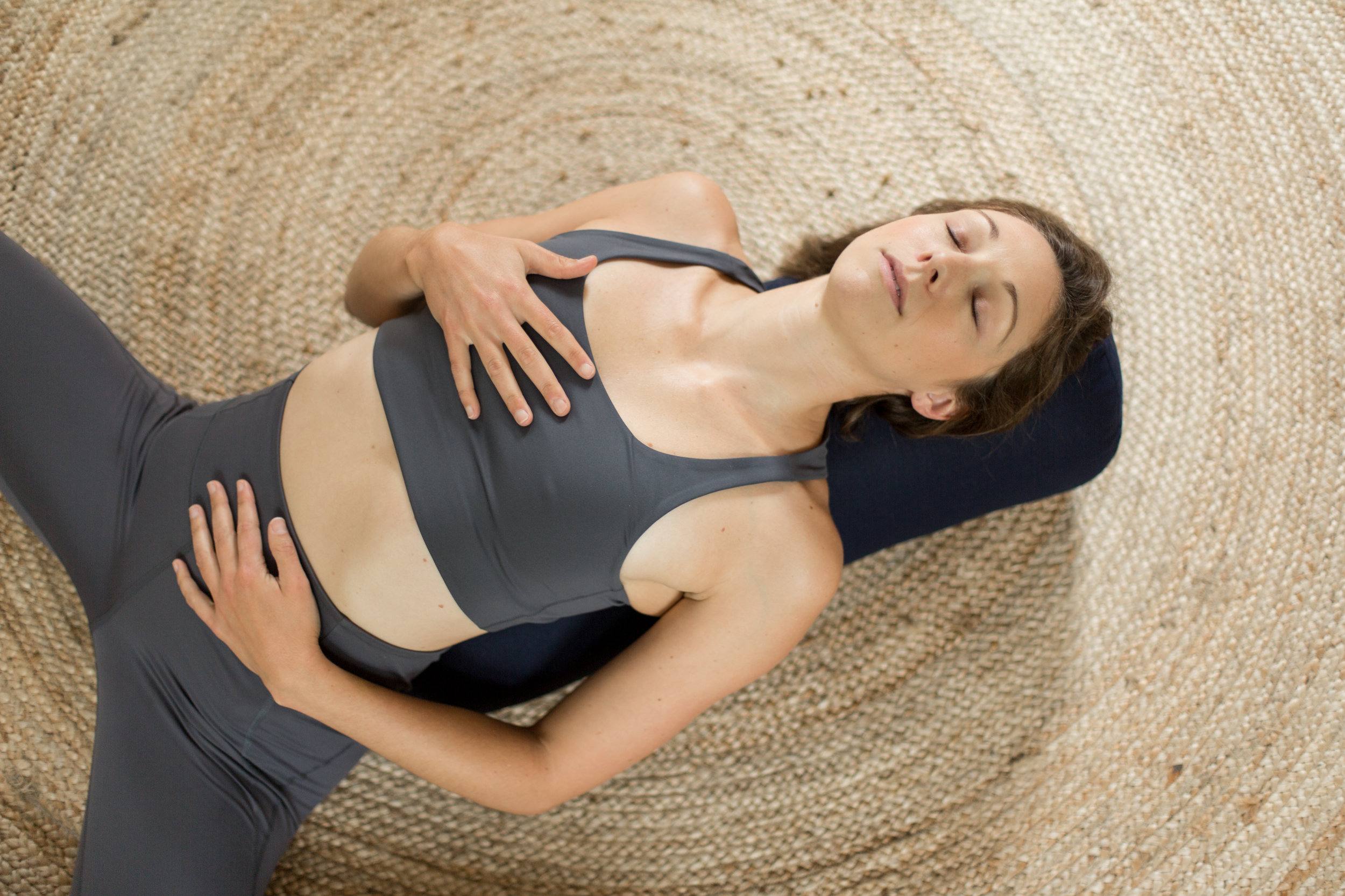 Women lying on a yoga bolster practicing restorative yoga. She has one hand on her heart and one hand on her chest and is focusing on breathing exercises to lower tension and stress.