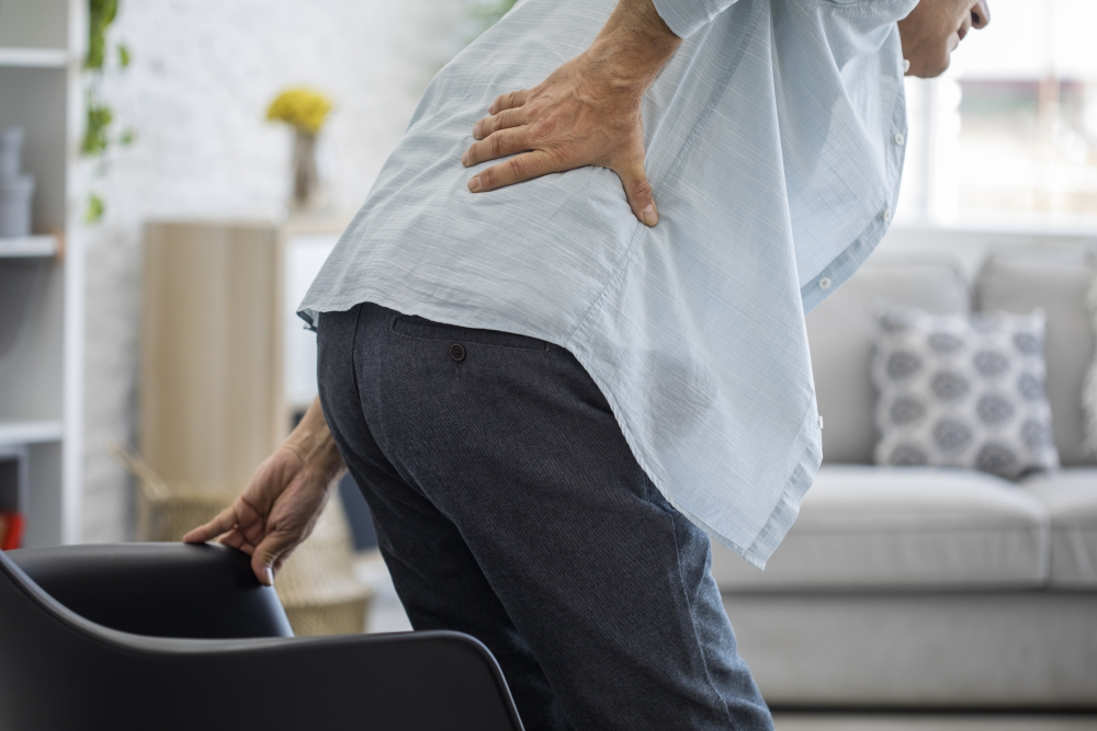 elderly man getting up from chair low back pain_degenerative-disk-disease-ddd_integrated-physicians-medical-group_the-integrated-brain-and-spine-center-for-functional-neurology-and-medicine.jpg