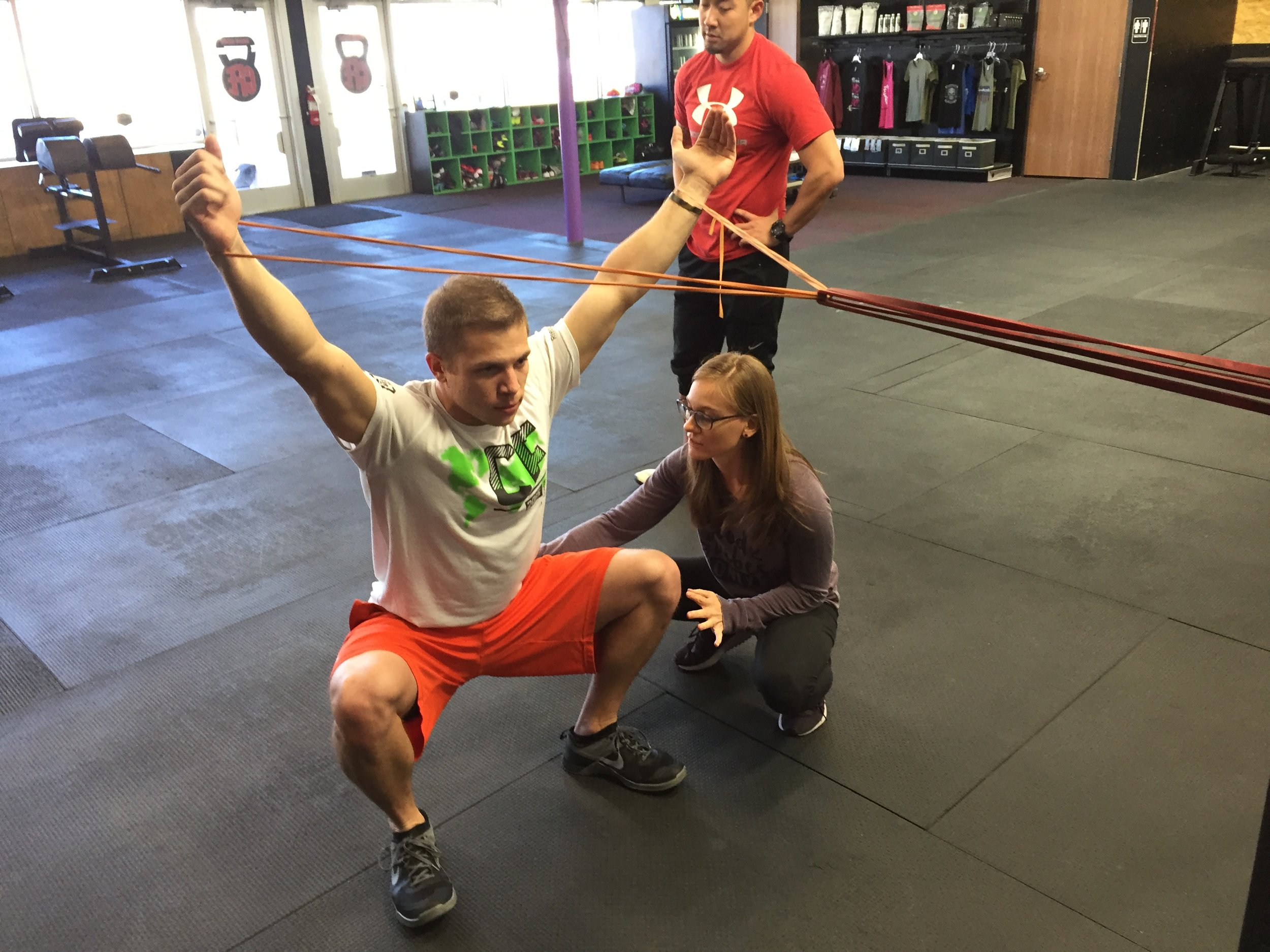 Teaching squat re-patterning cues to optimize position and activation. Here focused on getting diaphragm stacked over pelvic floor to maximize neuromotor control.