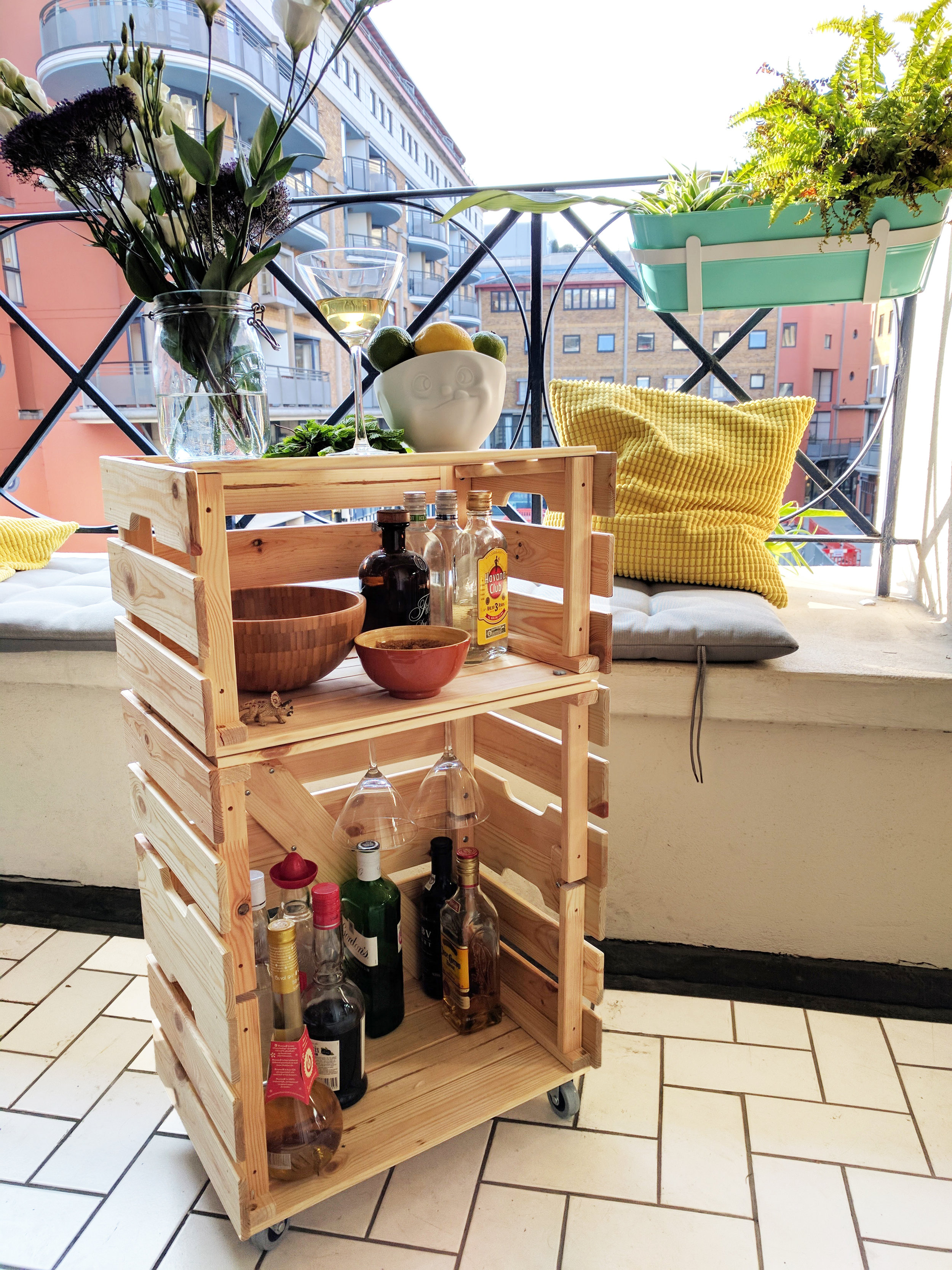 Cocktailcart out of refurbished wooden crates on sunny balcony