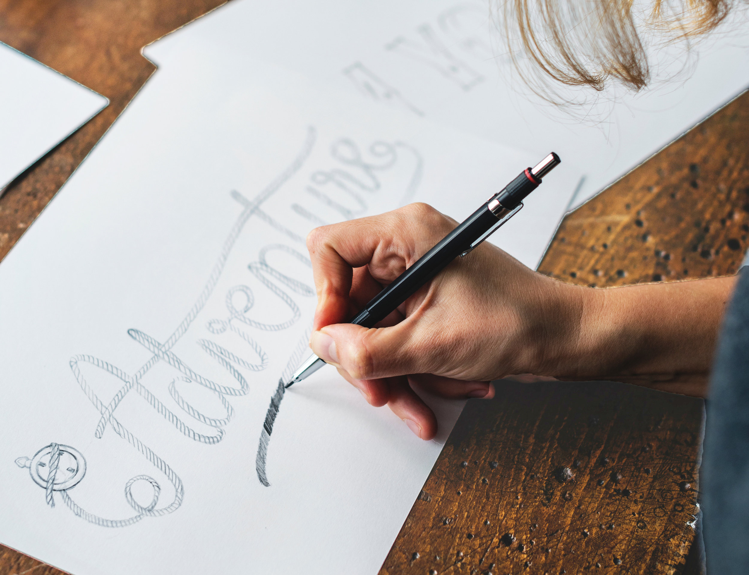 Woman using typography and drawing on pieces of paper