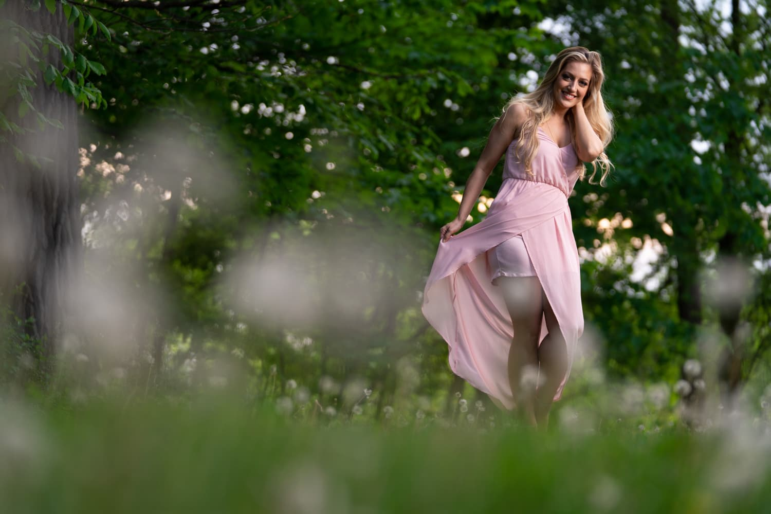 Blonde woman twirling pink dress in field of dandelions