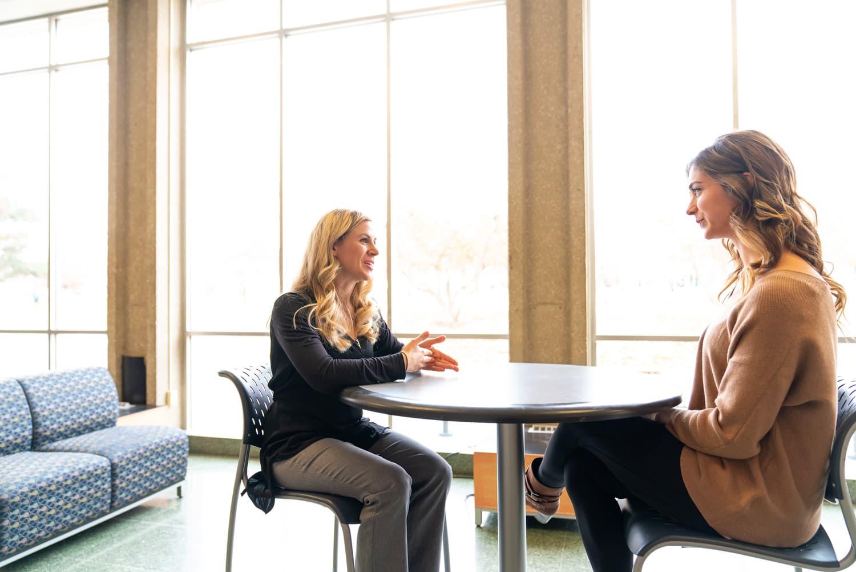 student and advisor talking near windows