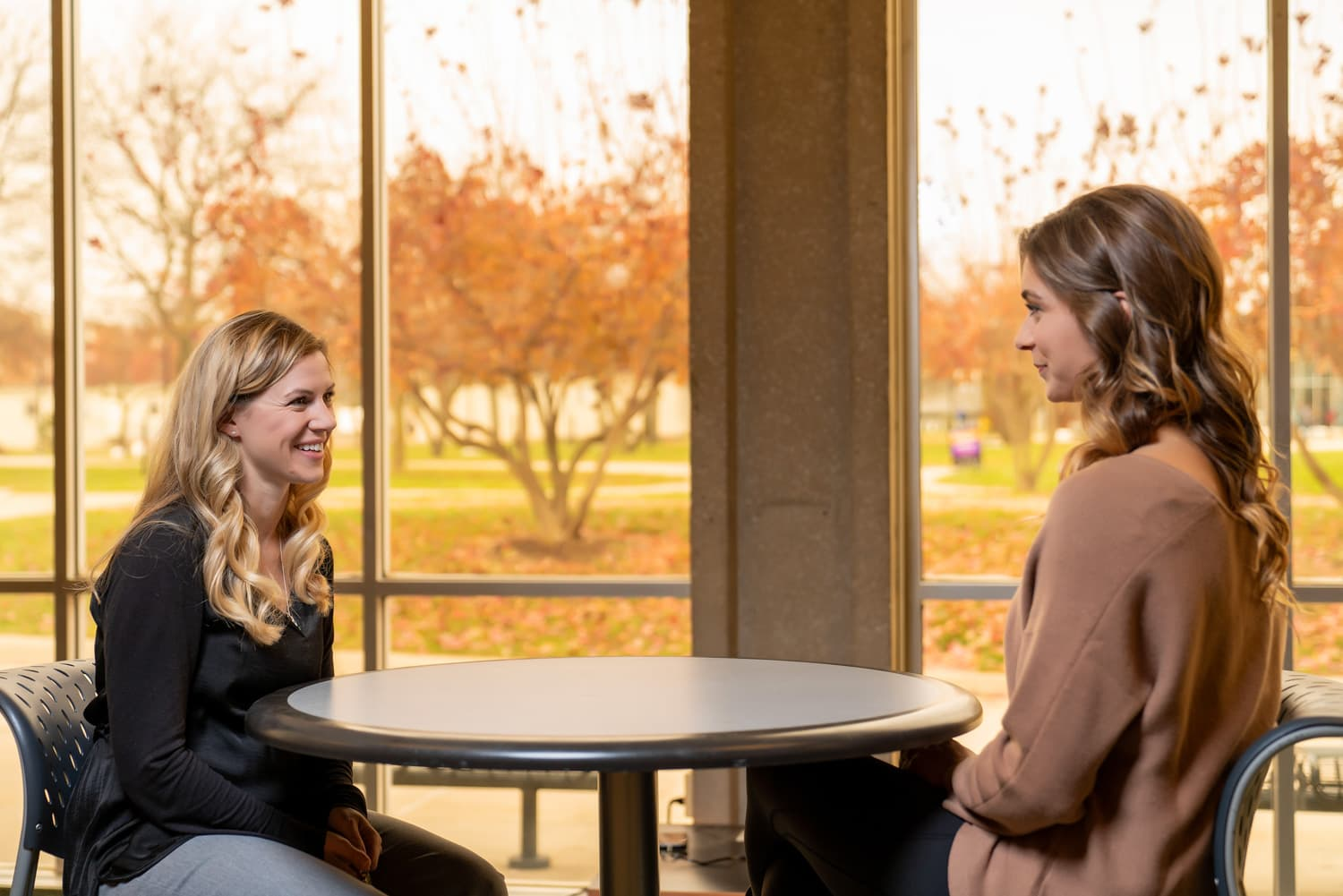 student and advisor talking at a table