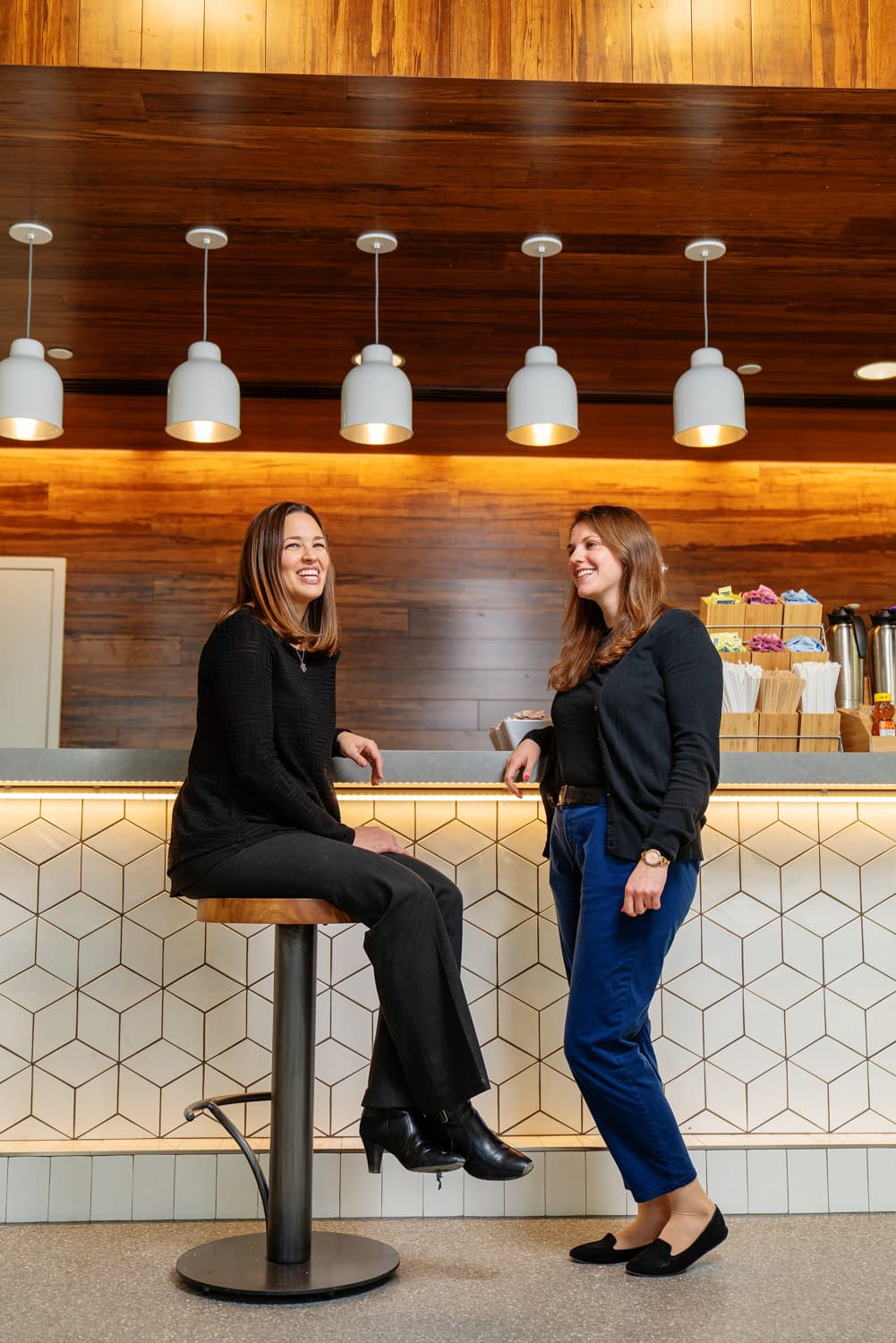 two people smiling at cafe counter
