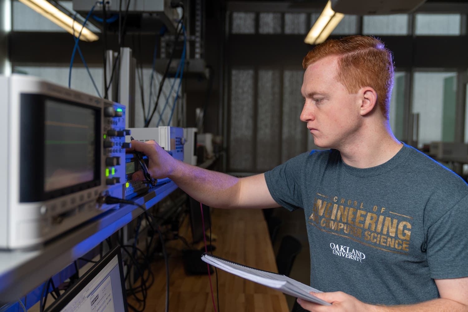 engineering student working with hardware at Oakland University School of Engineering and Computer Sciences