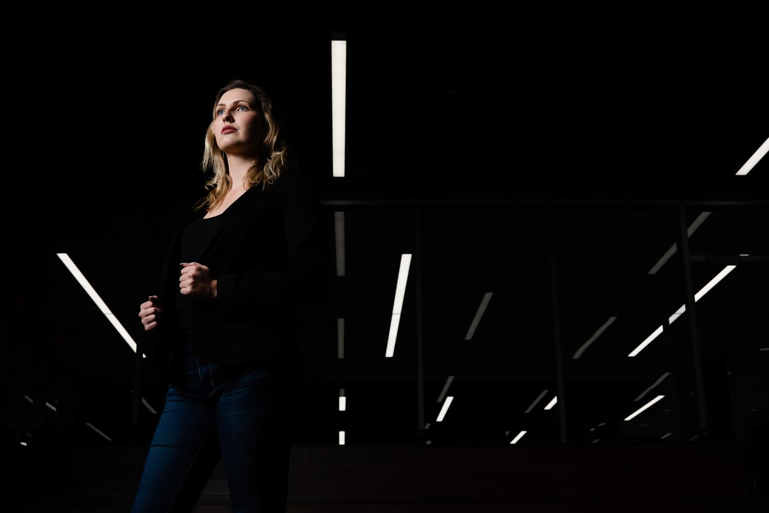 student standing looking off with lights in background
