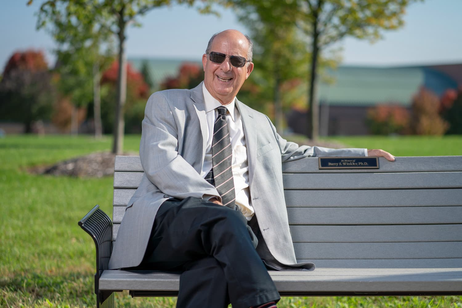 Doctor in sunglasses sitting on bench on campus.