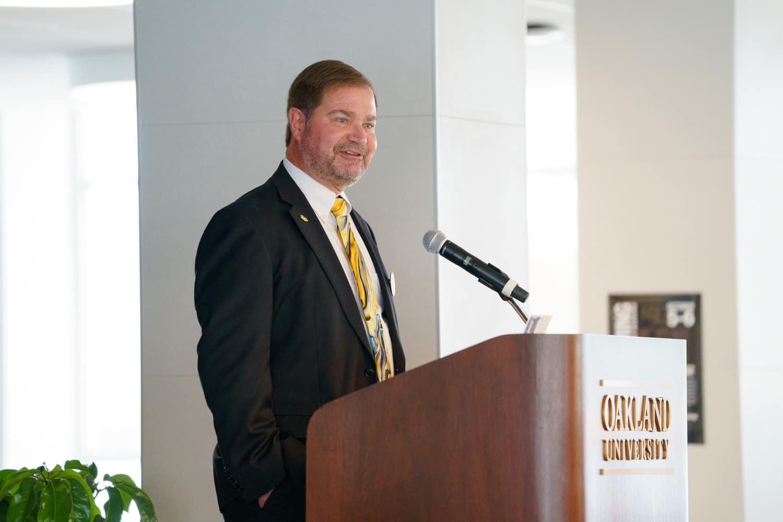 man in suit speaking at podium
