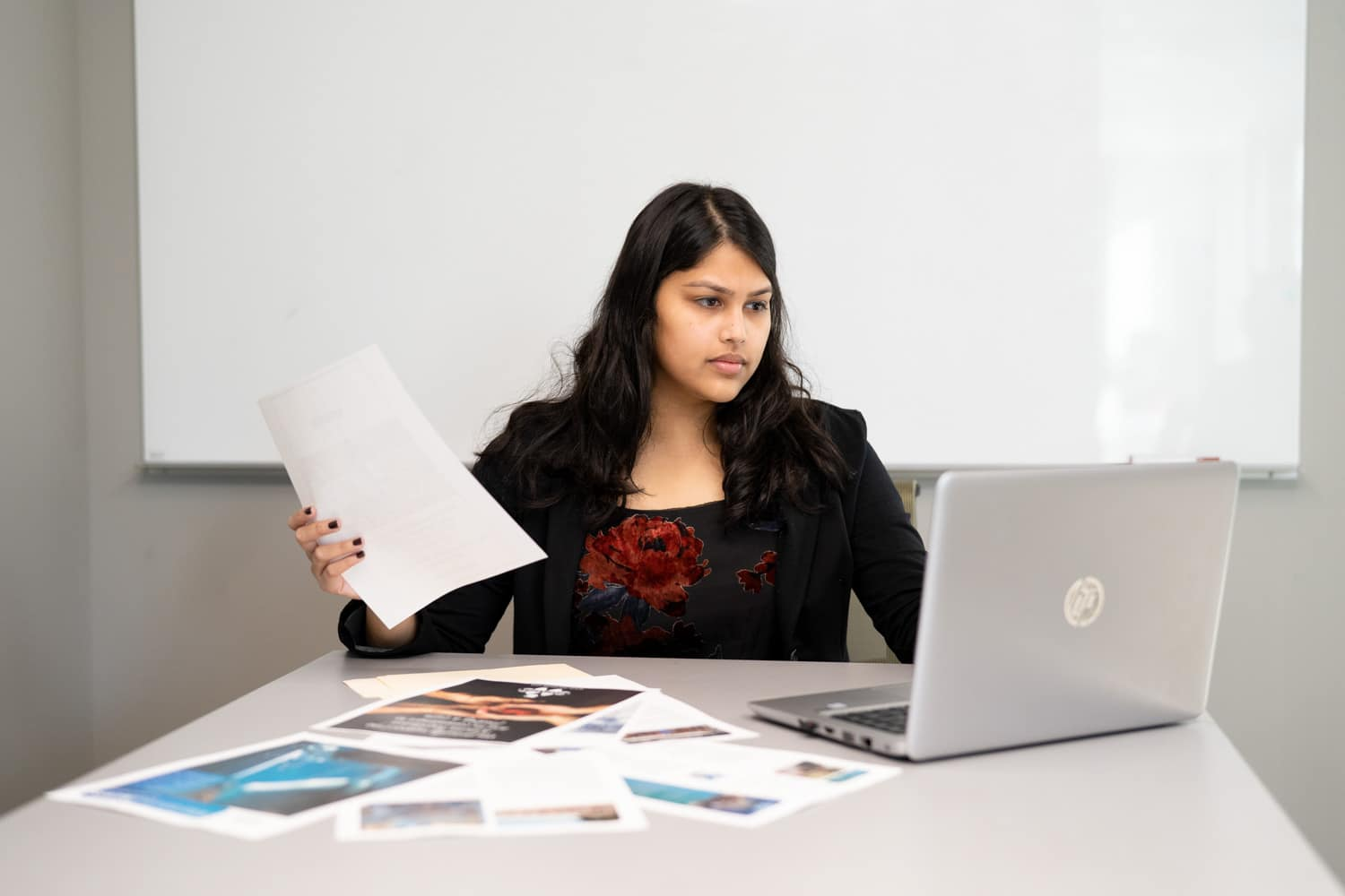 student holding paperwork while looking at macbook