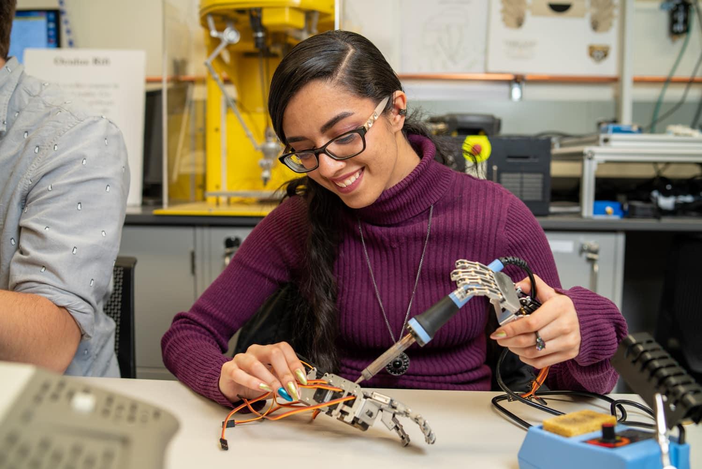 student soldering metal hand