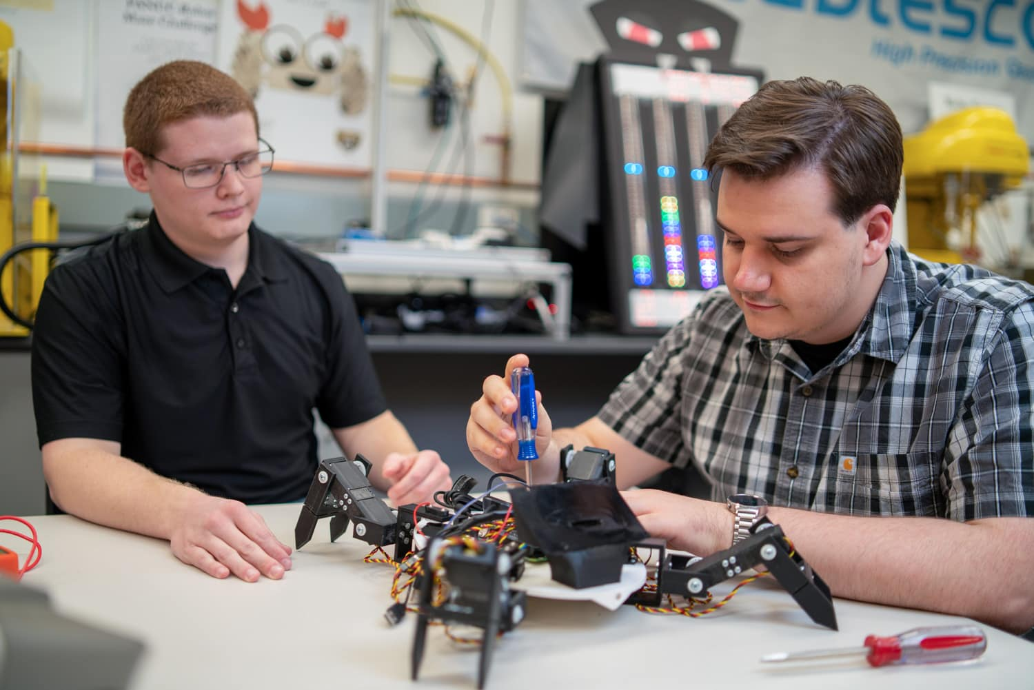 2 oakland university students working on a roboto