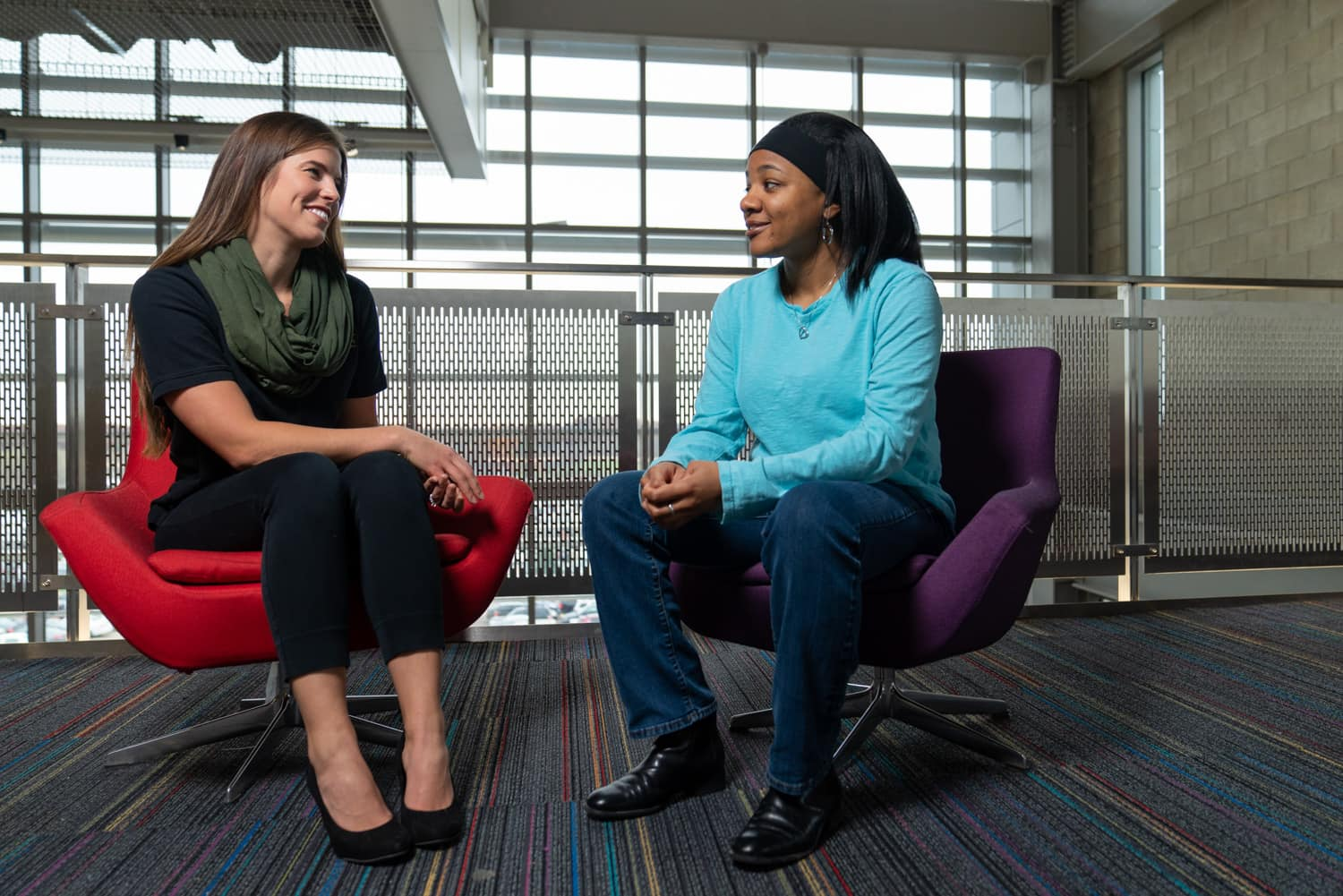 student and advisor talking in chairs in front of windows