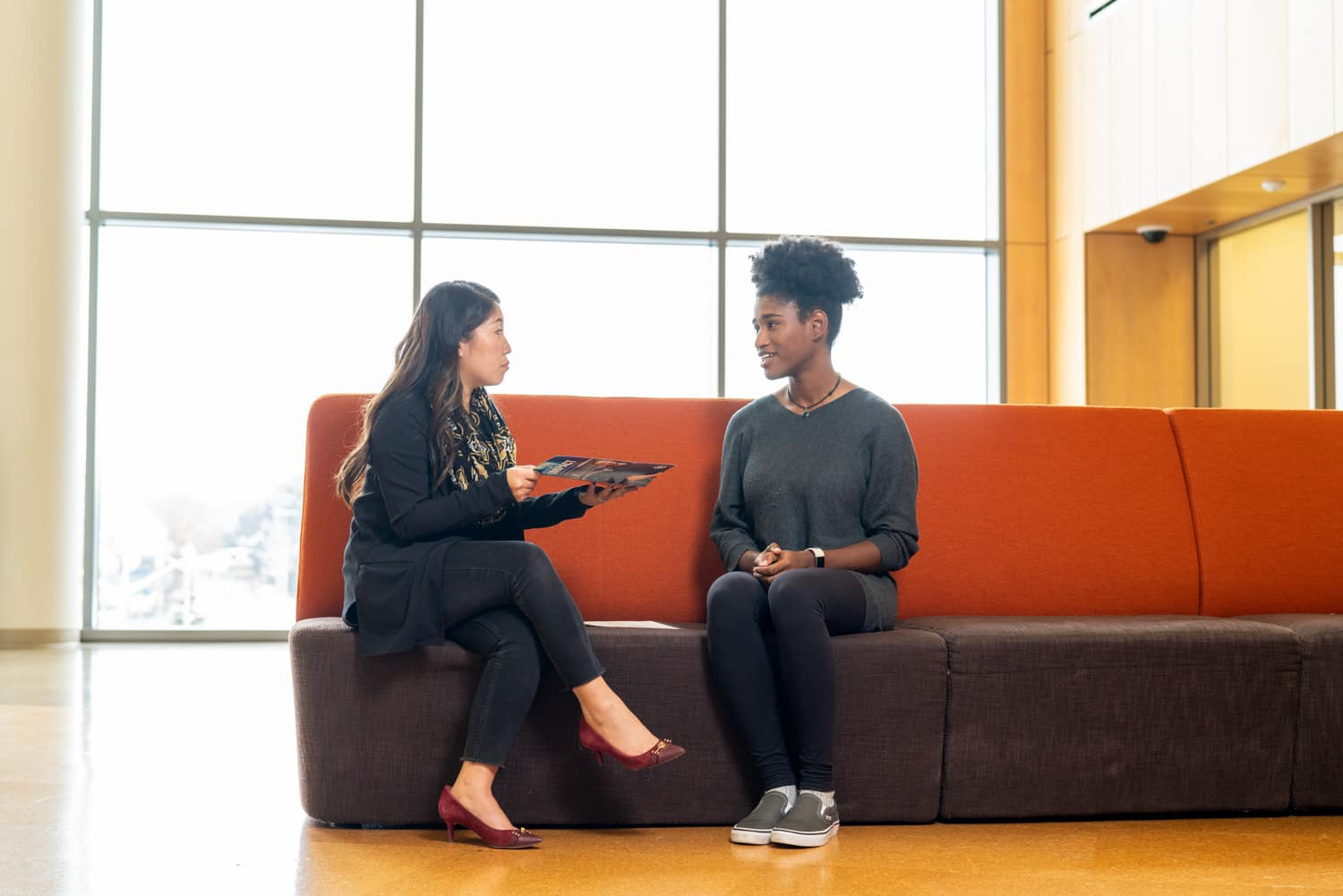 student and advisor discussing paperwork on couch