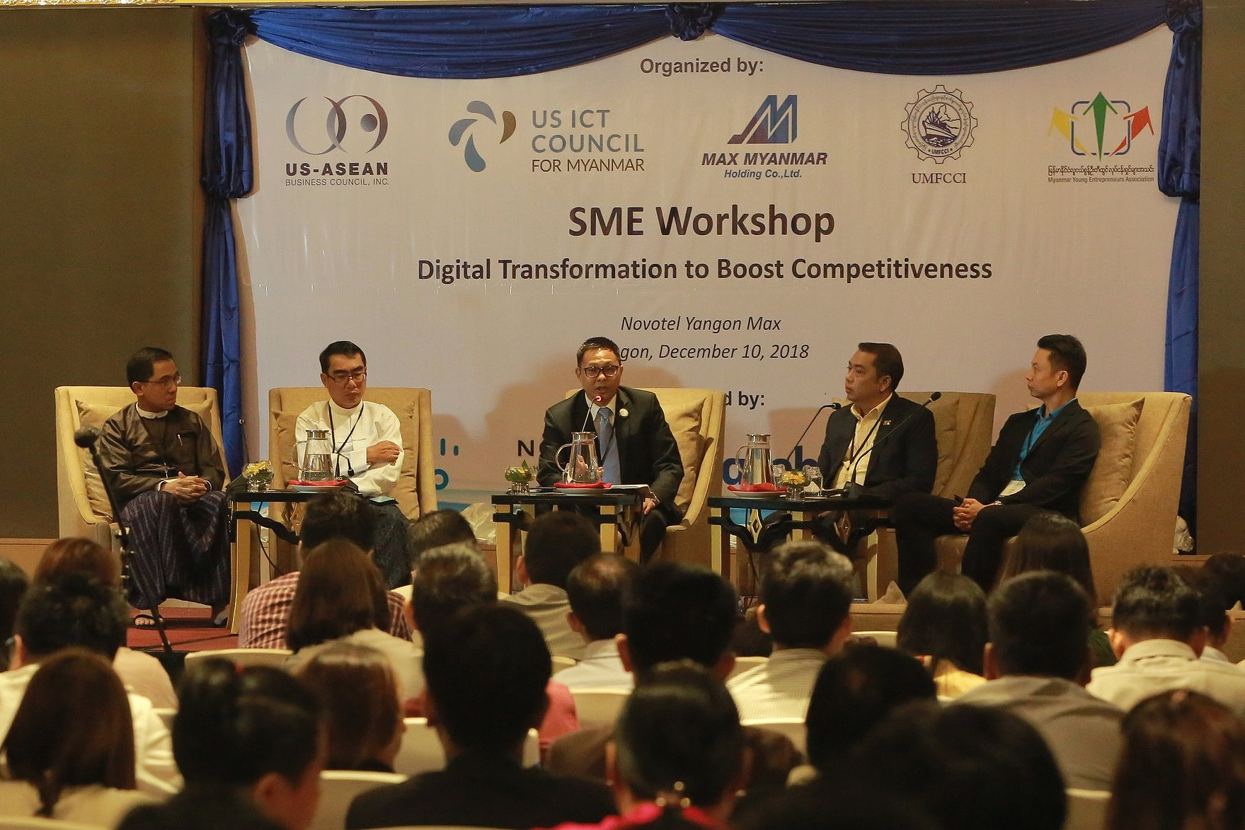 Max Myanmar CEO Chris Tun leads a panel discussion of industry leaders at an SME training workshop.