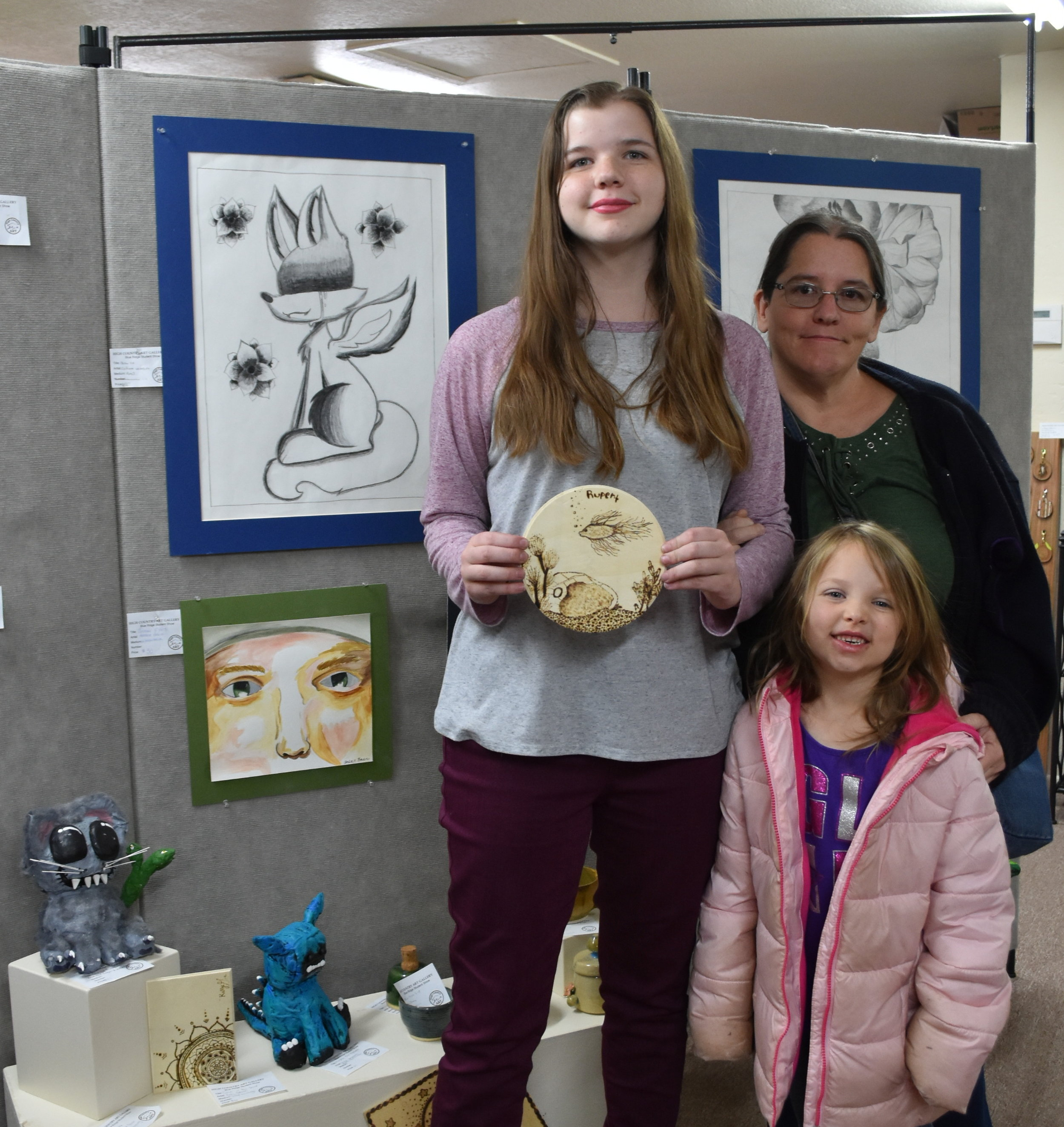 Copy of Amber Baer and Family, Amber holding one of her wood burning pieces.