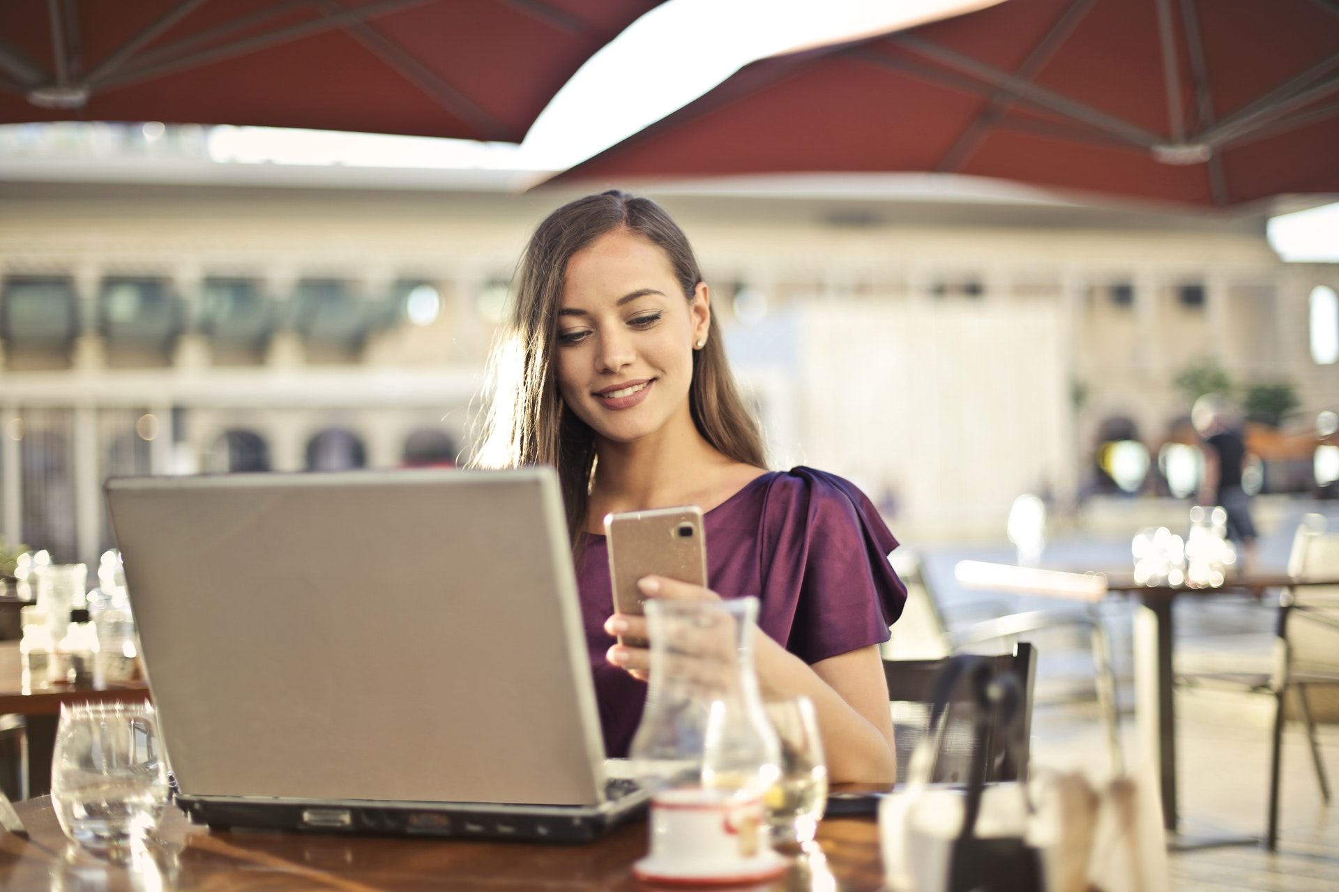 Woman sitting at a cafe with a laptop open, holding a phone | The Doula Consultant