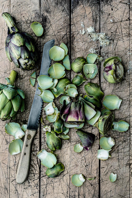 Artischocken putzen. Dafür die äußeren harten Blätter sehr großzügig entfernen, dann die obere Artischockenhälfte mit einem Sägemesser abschneiden und entfernen- veggielicious | gemüse. fotos. rezepte.