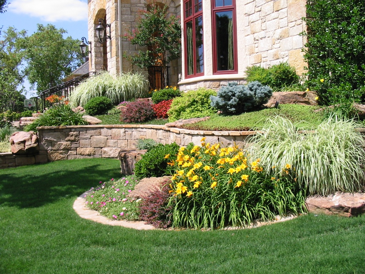 A stone retaining wall and classic stone steps are enhanced with the addition of color, texture and eye-appeal from an assortment of plants for hardscape designs.