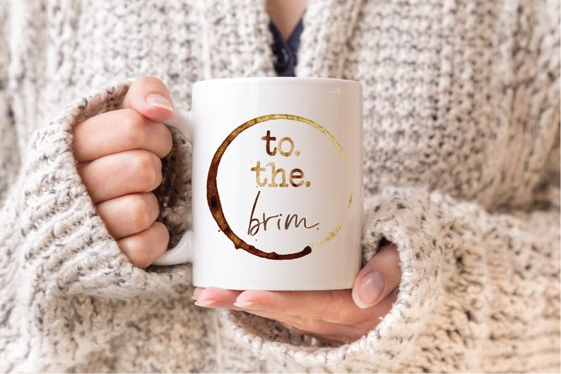 woman in sweater holding coffee cup