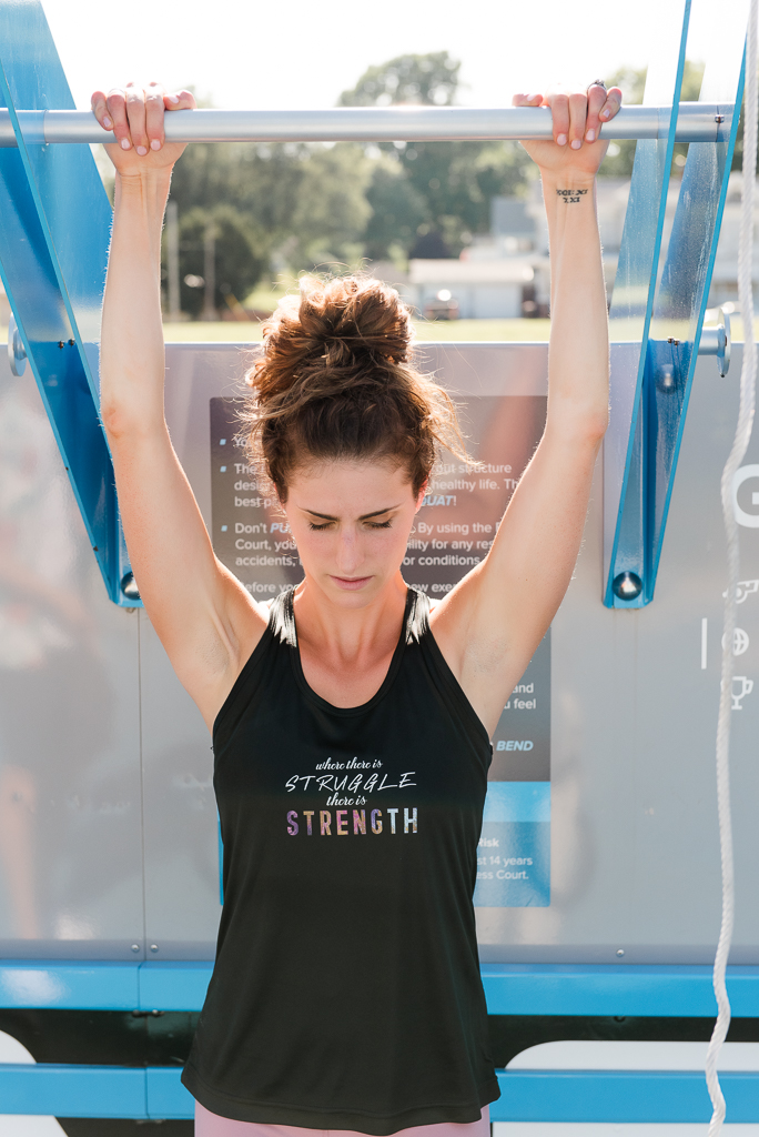 woman in black tank top working out arms raised