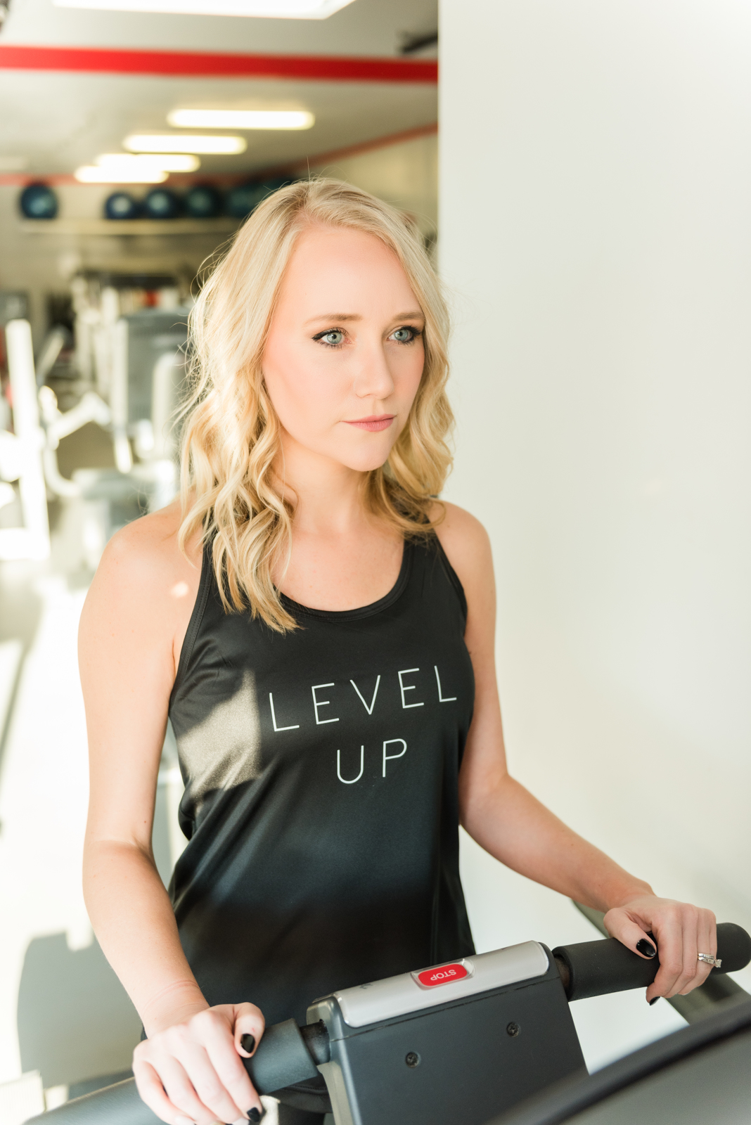 woman in black tank standing on treadmill