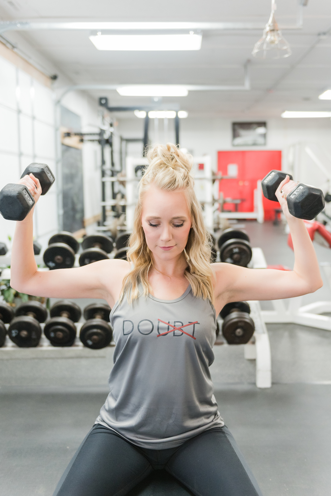 woman in gray tank lifting weights on weight bench