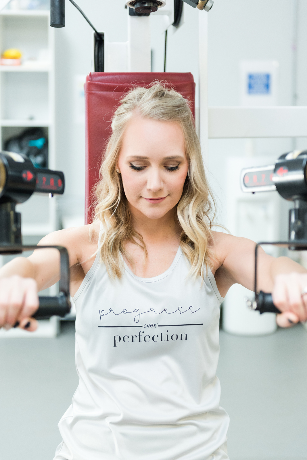 blonde woman using workout bench in white tank top