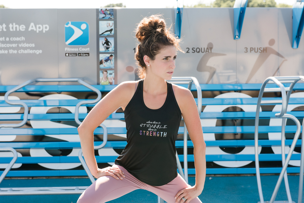 woman in blank tank stretching to workout