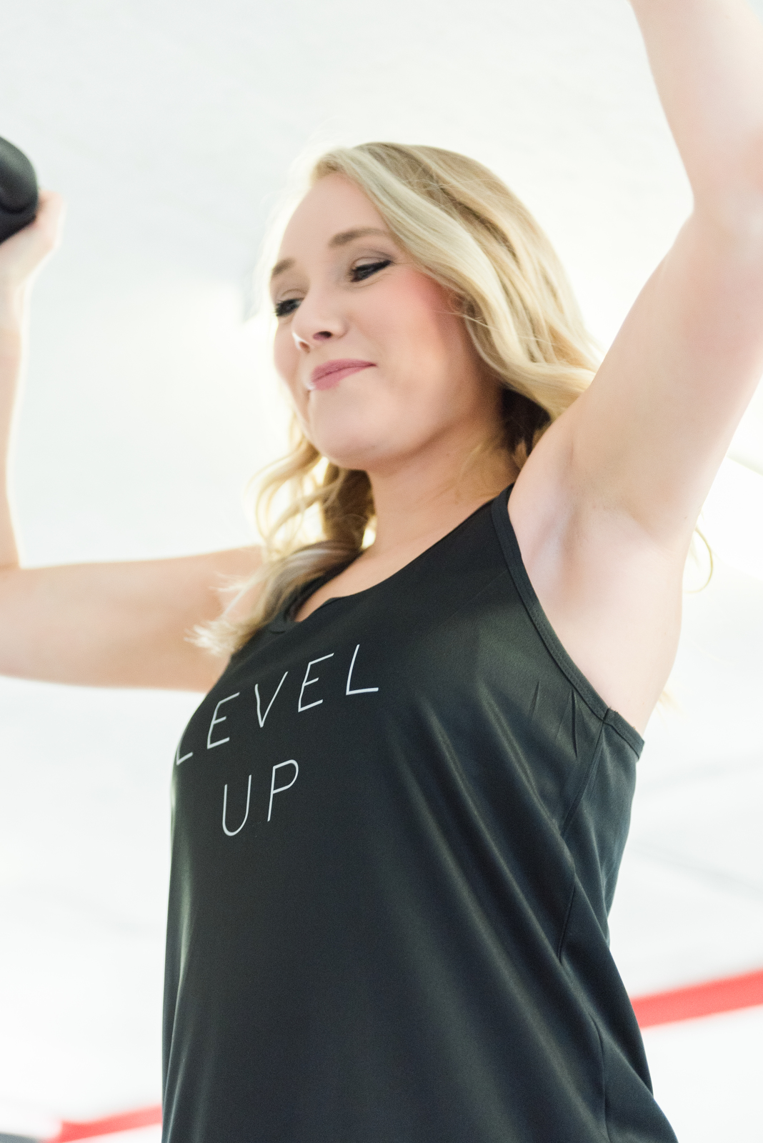 smiling woman working out in level up black tank