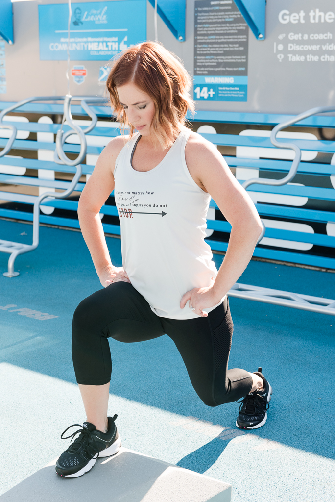 woman in white tank and black pants stepping up