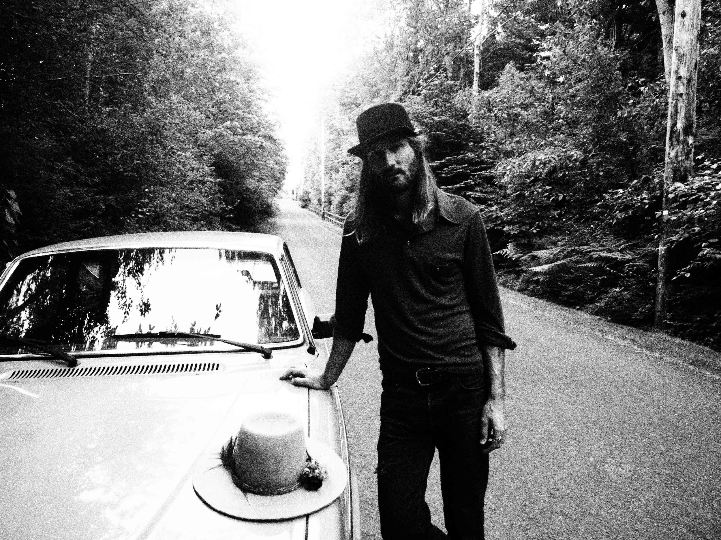 Braeden Paterson found standing with a hand-made hat, on location in the countryside of Vancouver Island, British Columbia, Canada.